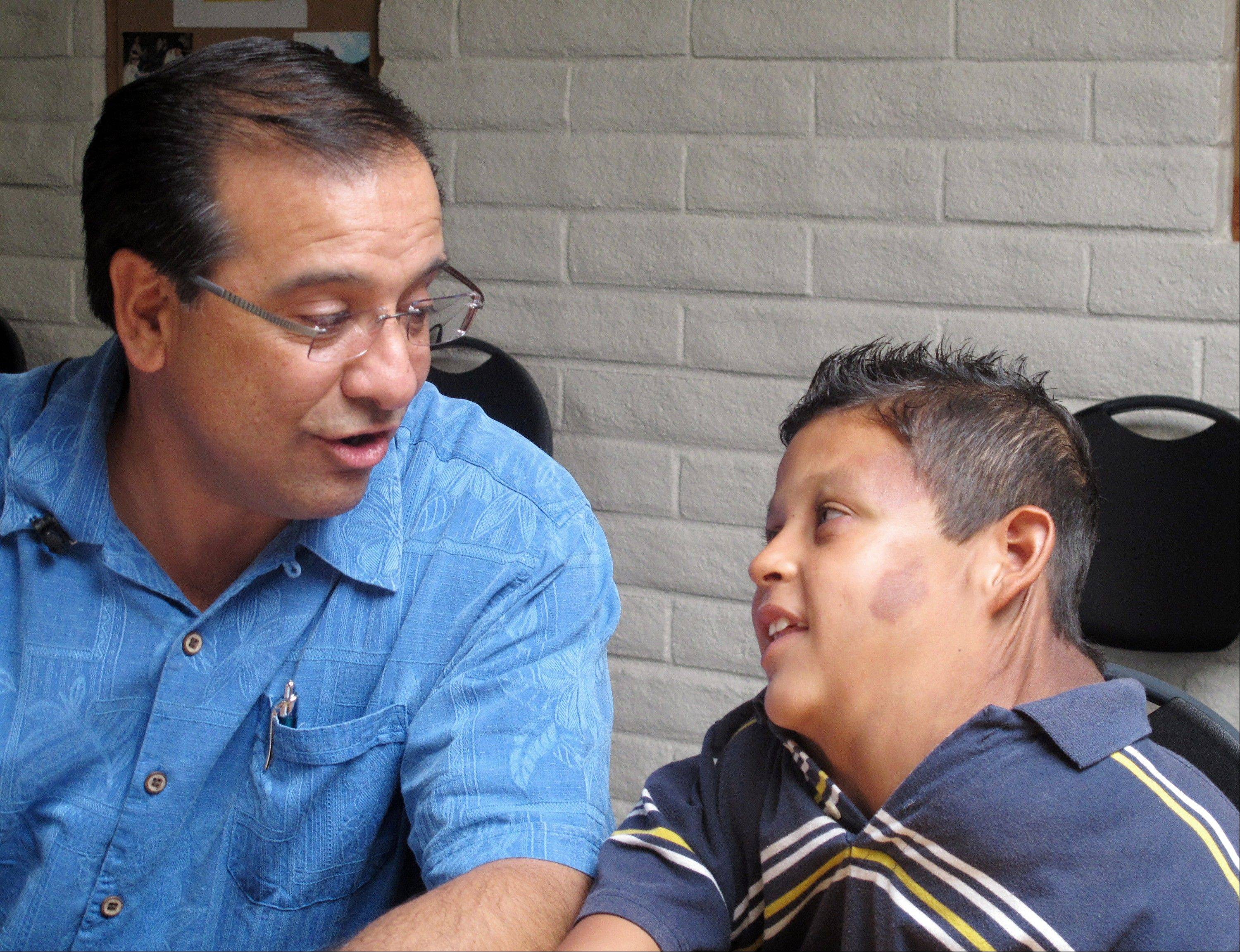 Si Budagher, the pastor of First Baptist Church of Rio Rancho, N.M. speaks Friday with a 9-year-old Juarez, Mexico-born boy suffering from massive tumor who U.S. Homeland Security identified only as �Jose.�