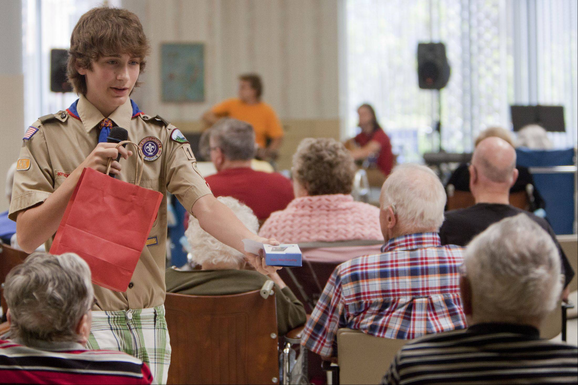 Christian Phillips, 14, of Mundelein and a member of Boy Scout Post 198 hands out a prize to a raffle winner during his volunteer project to put on a musical revue at the Winchester House nursing home in Libertyville. It was his final step to become an Eagle Scout.
