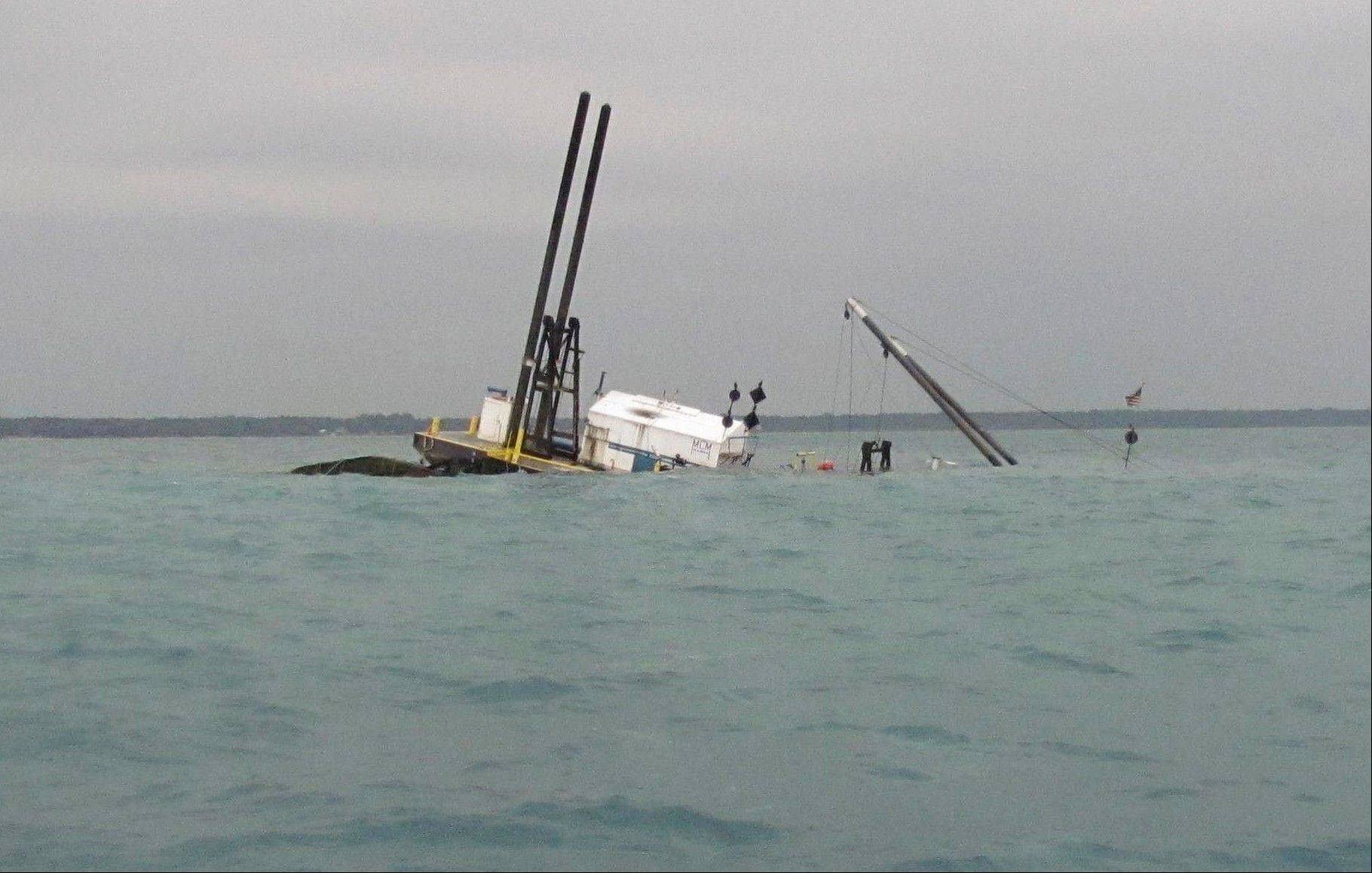 Part of a 110-foot commercial dredge, the Arthur J, can still be seen above the waters of Lake Huron after it sunk about 2 miles off Lakeport, Michigan, spilling an unknown amount of diesel fuel, early Thursday morning, July 19, 2012. The barge was carrying about 1,500 gallons of diesel fuel but it is uncertain how much escaped. St. Clair County Hazardous Material Team crews are working to contain the fuel with booms.