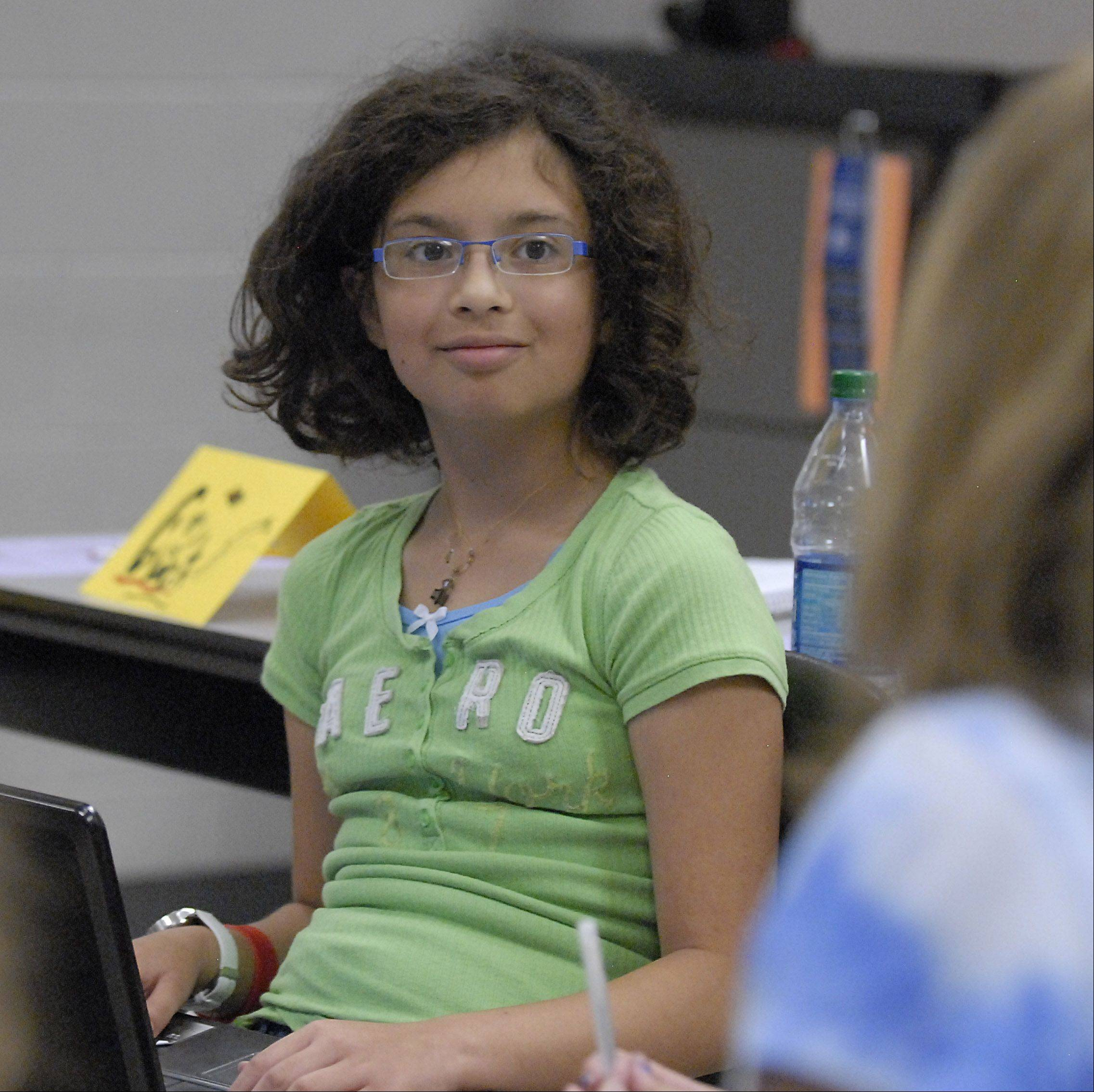"Jolie Guime, 12, of Elgin, listens as fellow classmates interpret a piece of her writing in the ""Writing Academy"" class at Elgin Community College's Kids' College program last week. Students rewrote a portion of a story they were all reading and then discussed their alternate scenarios."