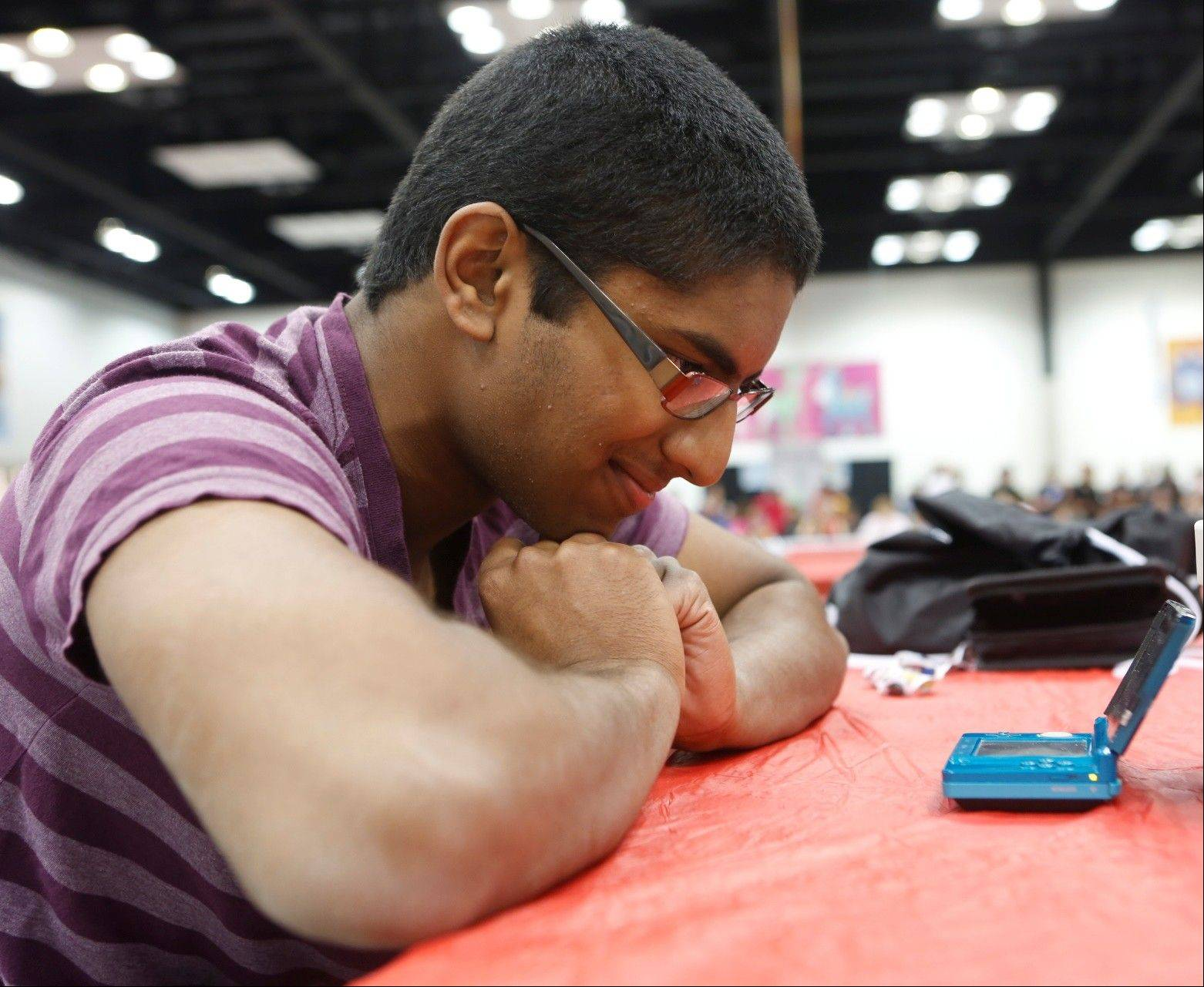 Des Plaines resident Manoj Sunny, 16, gazes at his Nintendo DS during the Pok�mon National Championships in Indianapolis earlier this month. Sunny, who finished in fourth place, will travel to Hawaii for the world championships next month.