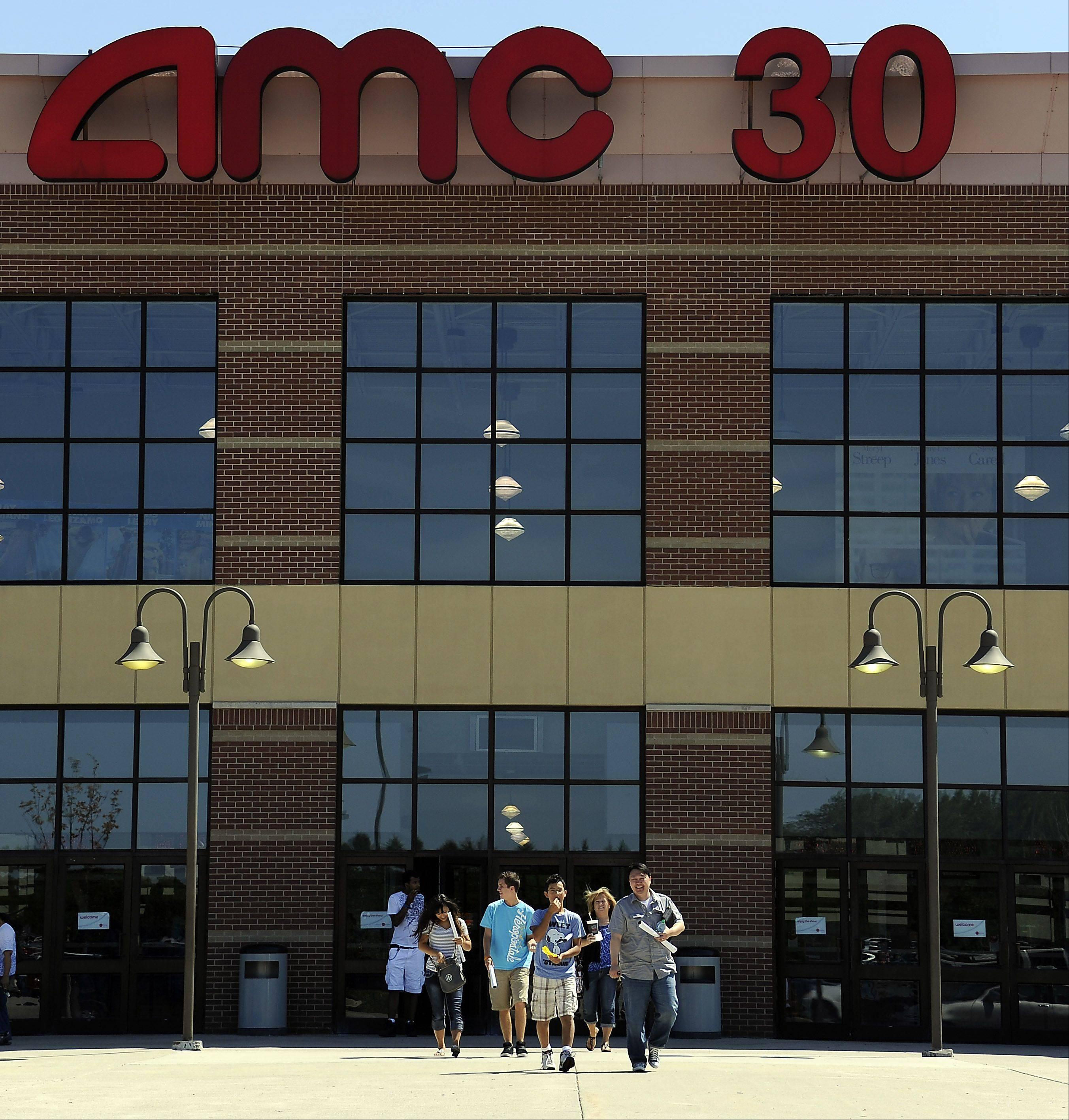 "Patrons walk out of the AMC 30 theaters in South Barrington after having attended an opening day showing of ""The Dark Knight Rises."" Theaters across the suburbs spent Friday addressing security concerns raised by the mass shooting at a Denver-area showing of the new Batman film."