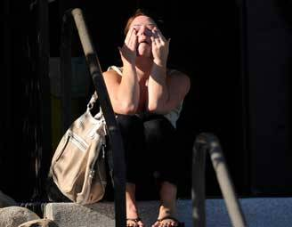Amanda Medek, who is looking for her sister Micayla, sits outside Gateway High School Friday in Aurora, Colorado.