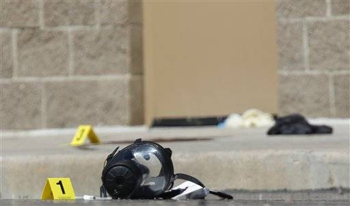 Yellow markers sit next to evidence, including a gas mask, as police investigate the scene outside the Century 16 movie theater east of the Aurora Mall in Aurora, Colo. on Friday, July 20, 2012. A gunman in a gas mask barged into a crowded Denver-area theater during a midnight showing of the Batman movie on Friday, hurled a gas canister and then opened fire in one of the deadliest mass shootings in recent U.S. history.