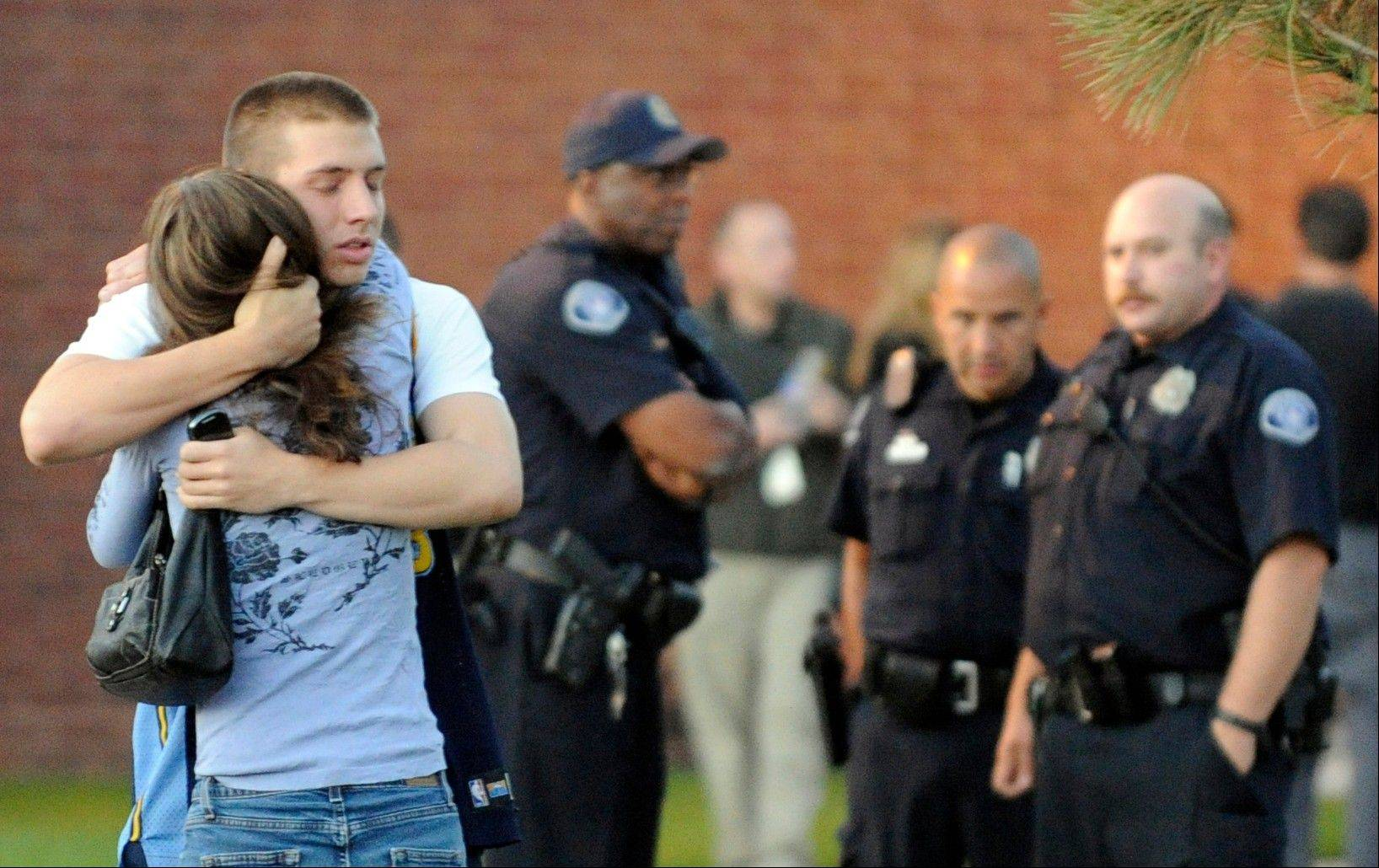 Eyewitness Jacob Stevens, 18, hugs his mother, Tammi Stevens, after being interviewed by police Friday outside Gateway High School where witnesses were brought for questioning after a mass shooting at a movie theater in Aurora, Colo.