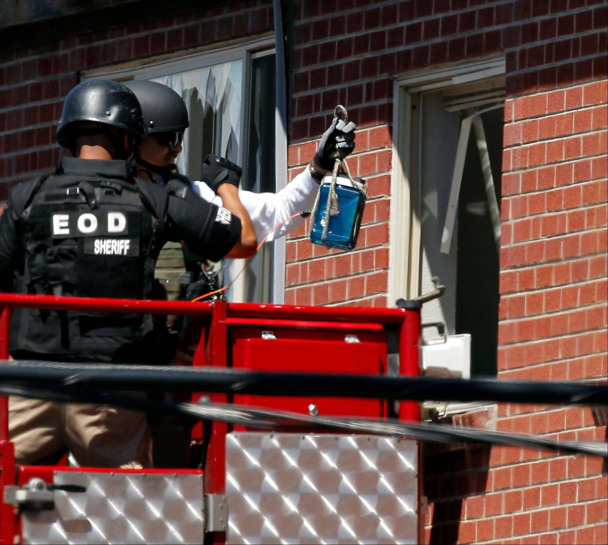 "Members of law enforcement wearing body armor and helmets prepare to what ATF sources describe as a""water shot"" in the apartment of alleged gunman James Holmes Saturday, July 21, 2012 in Aurora , Colo. The ""water shot"" is exploded and used to disrupt the device. Authorities reported that 12 died and more than three dozen people were shot during an assault at a movie theatre midnight premiere of ""The Dark Knight Rises."""