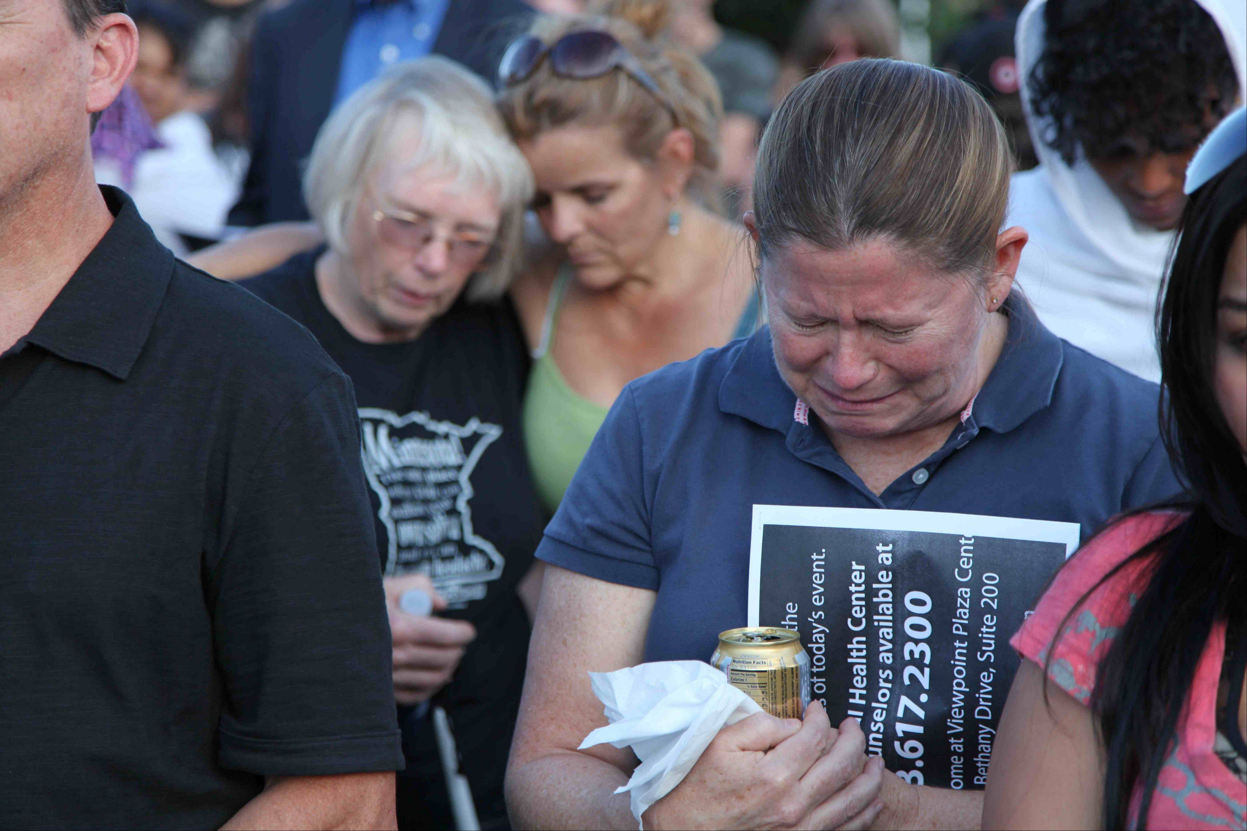 "People mourn at a vigil, Friday, July 20, 2012 in Aurora, Colo. Authorities report that 12 died and more than three dozen people were shot during an assault at the theatre during a midnight premiere of ""The Dark Knight."""