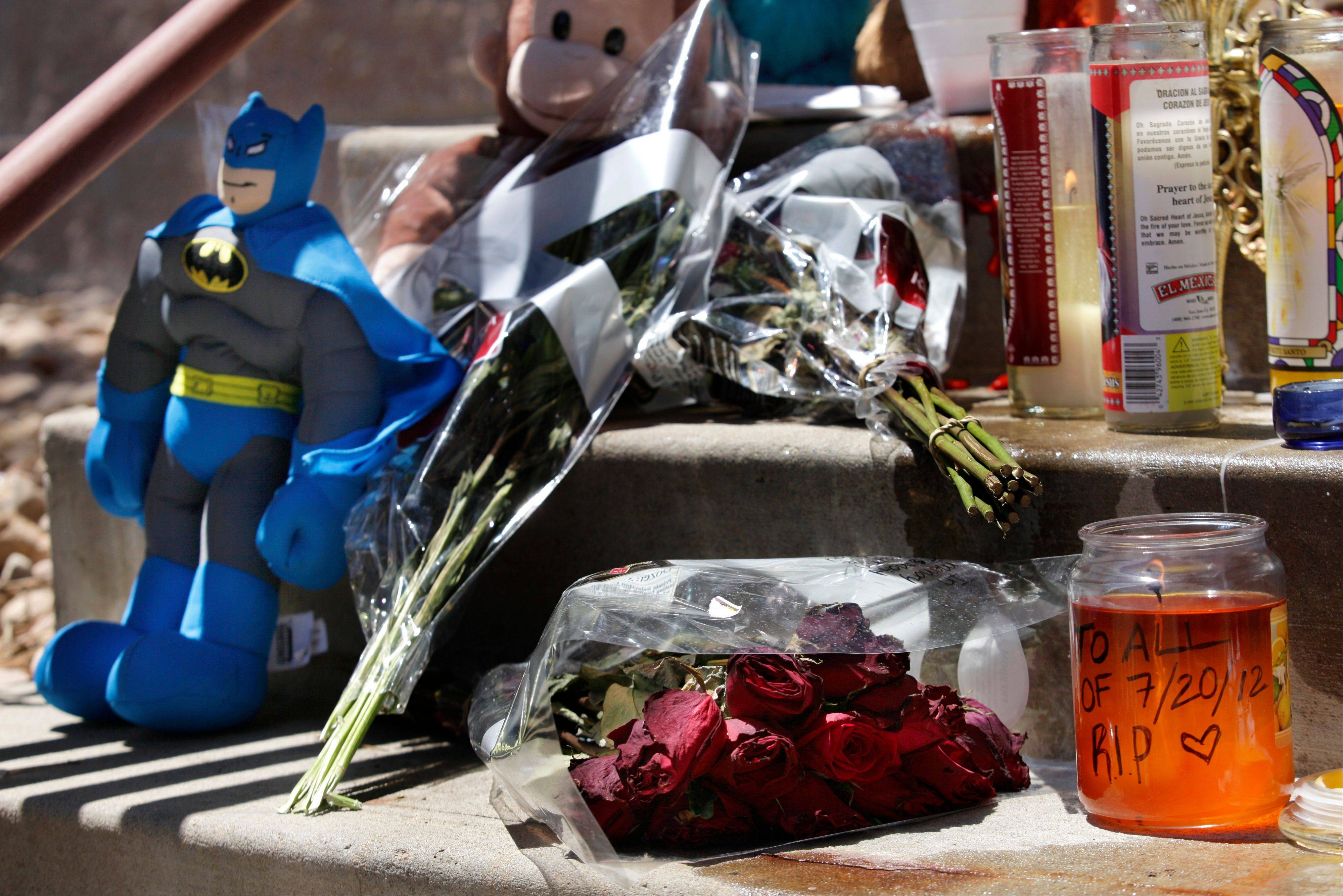 "Candles, flowers and a Batman figure are shown at a memorial Saturday in Aurora, Colo. Twelve people were killed and dozens were injured in a shooting attack early Friday at the packed theater during a showing of the Batman movie, ""The Dark Knight Rises."" The shooting has moviegoers and movie theaters worried about the long-standing tradition of midnight movies. Some people are reconsidering going to midnight showings, and AMC has banned costumes and face-covering masks."