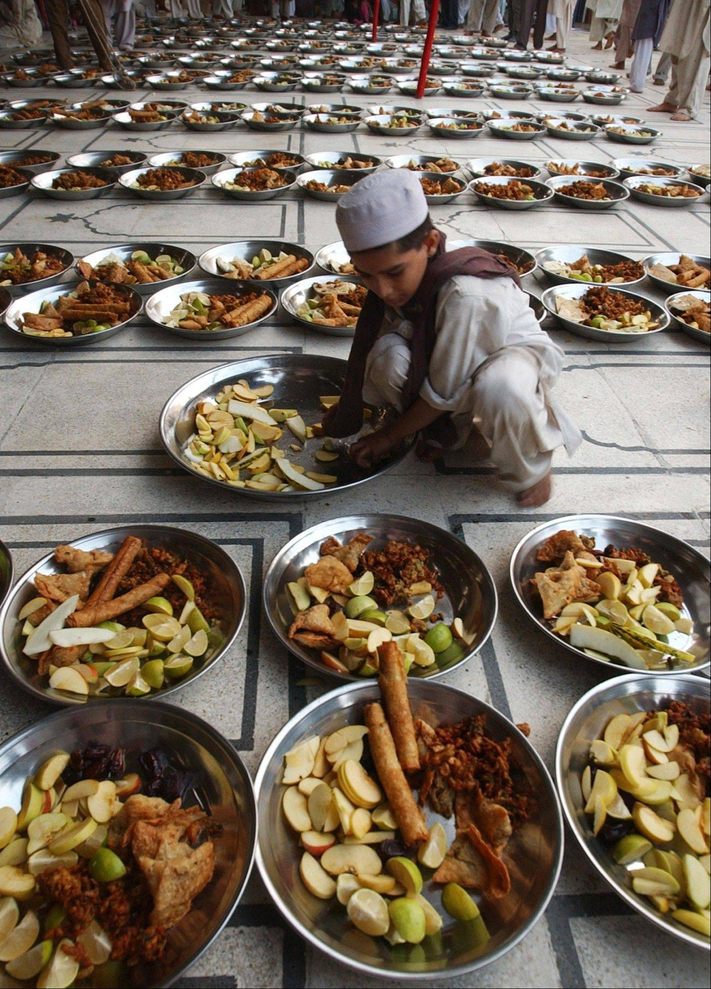 In this image taken on Sept. 25, 2006, a Pakistani boy arranges dishes of fruits and other items for Muslims to break their first fast at a local mosque in Karachi, Pakistan. During Ramadan observant Muslims refrain during daylight hours from eating, drinking and smoking.