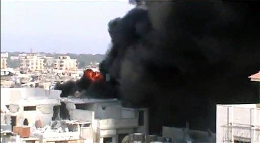 This image made from amateur video released by Shaam News Network and accessed by the Associated Press Saturday, July 21, purports to show the spread of fires as a result of the shelling of Homs, Syria by government forces on July 21.