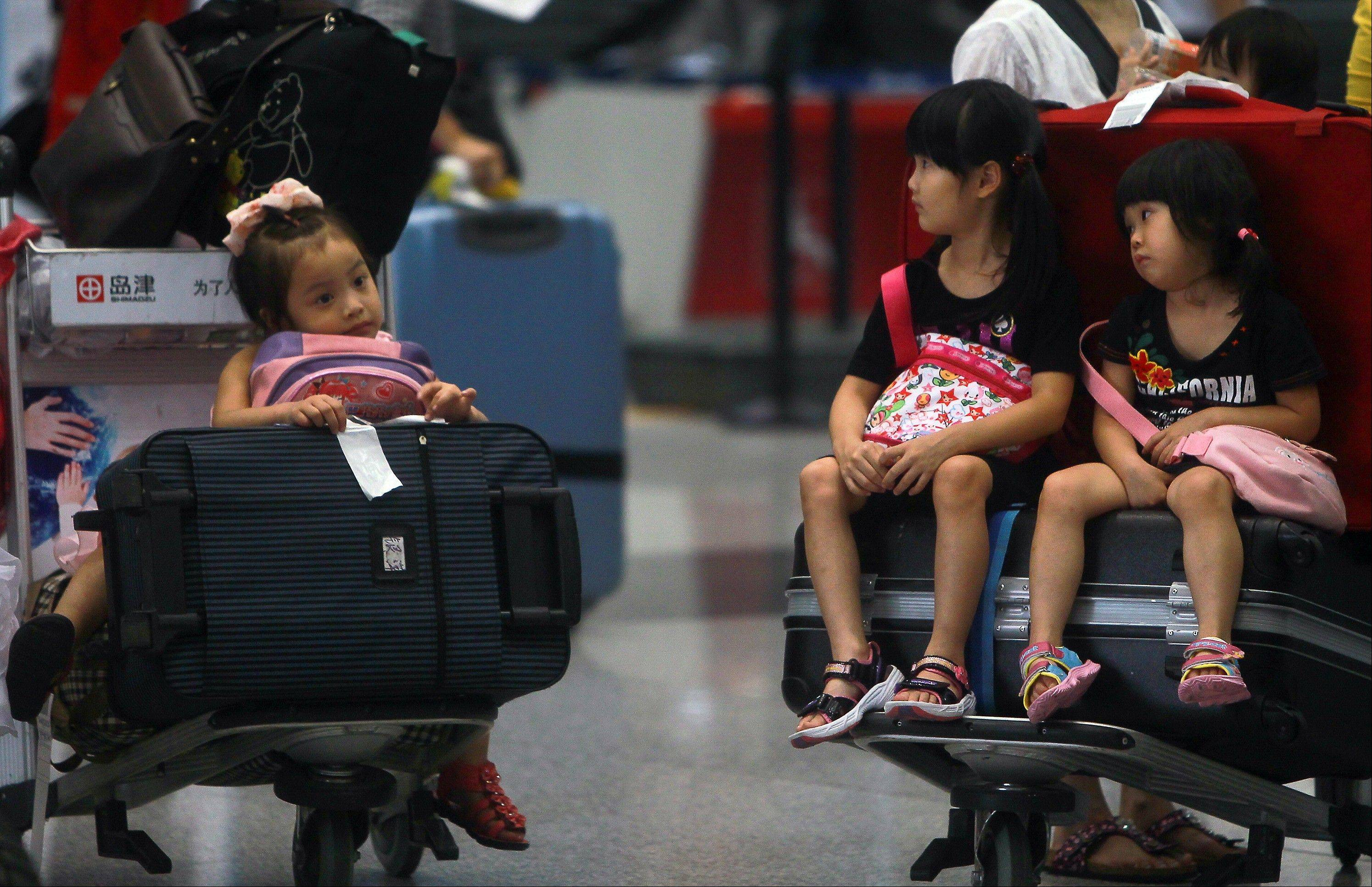 Children sit on the luggage carts Saturday as they stranded at the Beijing Capital International Airport after flights are canceled due to the heavy rains.