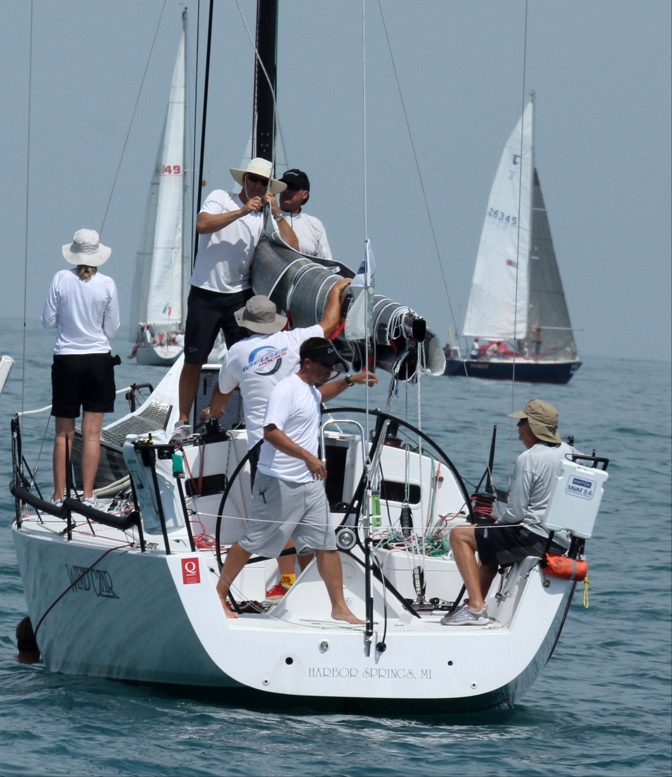 Crew members on board Wind Czar owned by Richard Lehmann, of Paradise Valley, AZ, from Little Traverse Yacht Club, prepare to raise the sail for the start of the 104th Chicago Yacht Club Race to Mackinac on Lake Michigan of Chicago on Saturday, July 21.