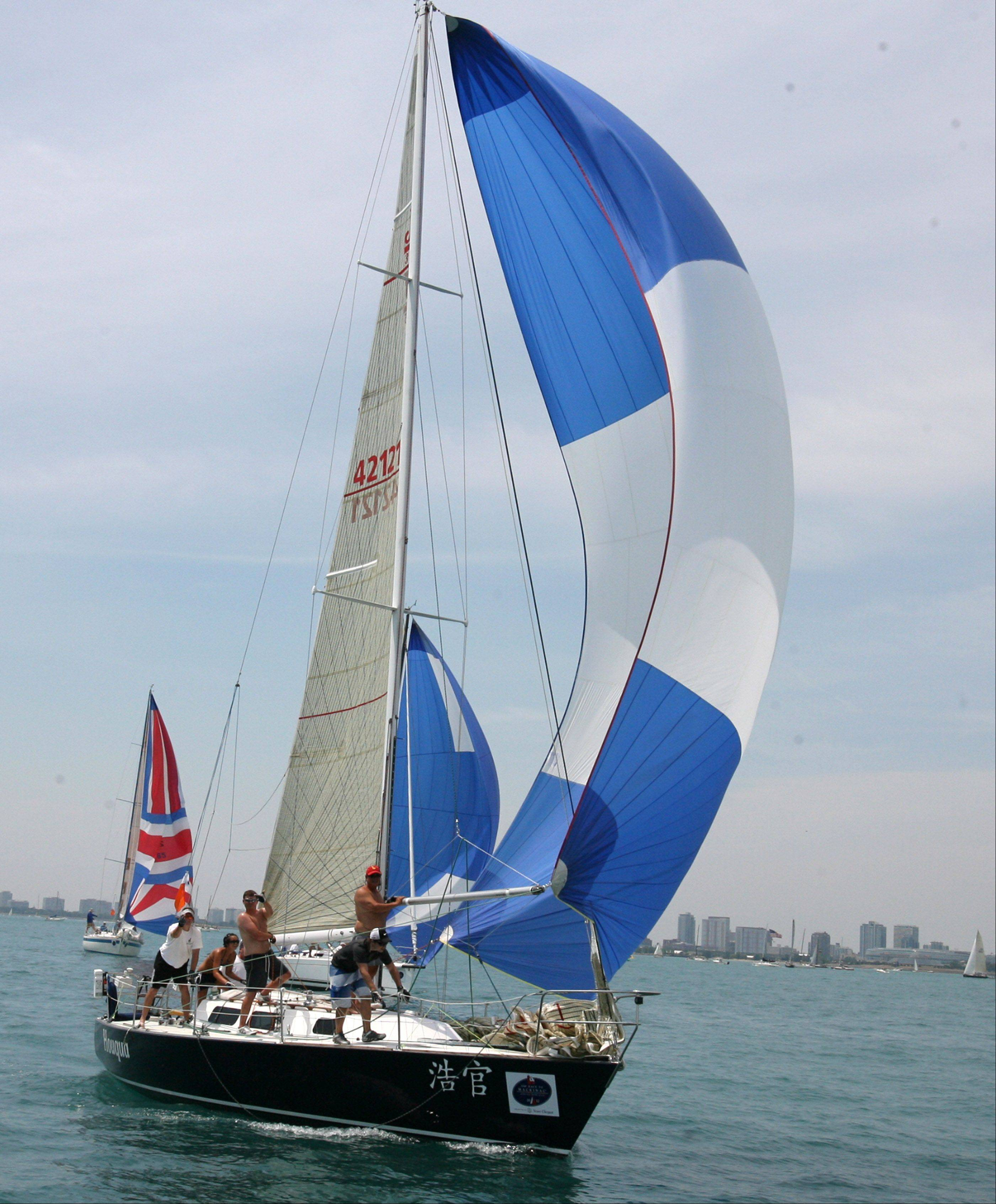 The crew of Houqua, USA 4212, owned by Jack Andree, of Muskegon, MI, with Muskegon Yacht Club is able to get a little wind in the boats sail.