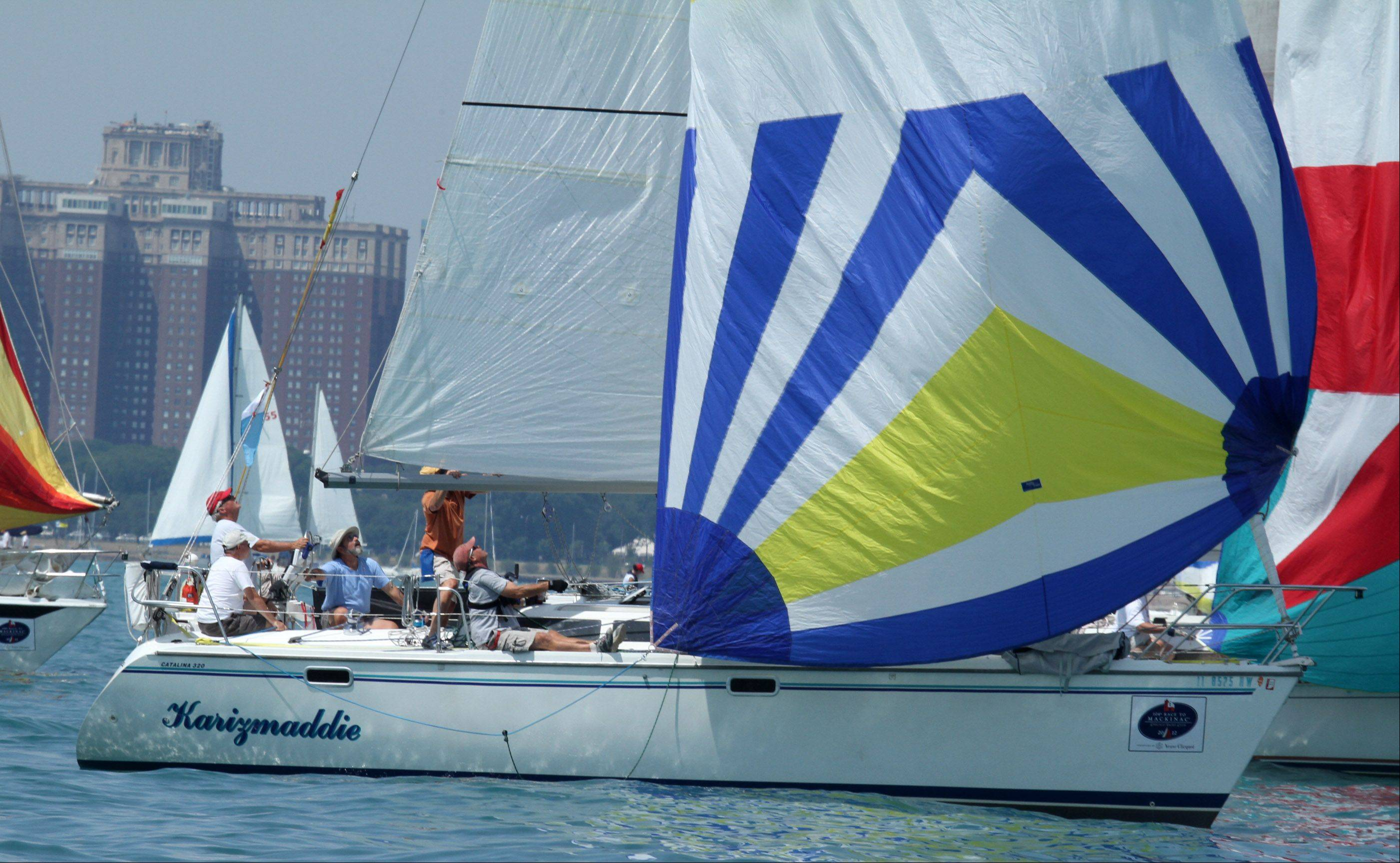Crew of the Karizmaddie, USA 50662, owned by Patrick Reynolds and Linda Sadlowski, of Chicago, with Hammond Yacht Club get wind int the sail at the start of the 104th Chicago Yacht Club Race to Mackinac on Lake Michigan near Chicago on Saturday, July 21.