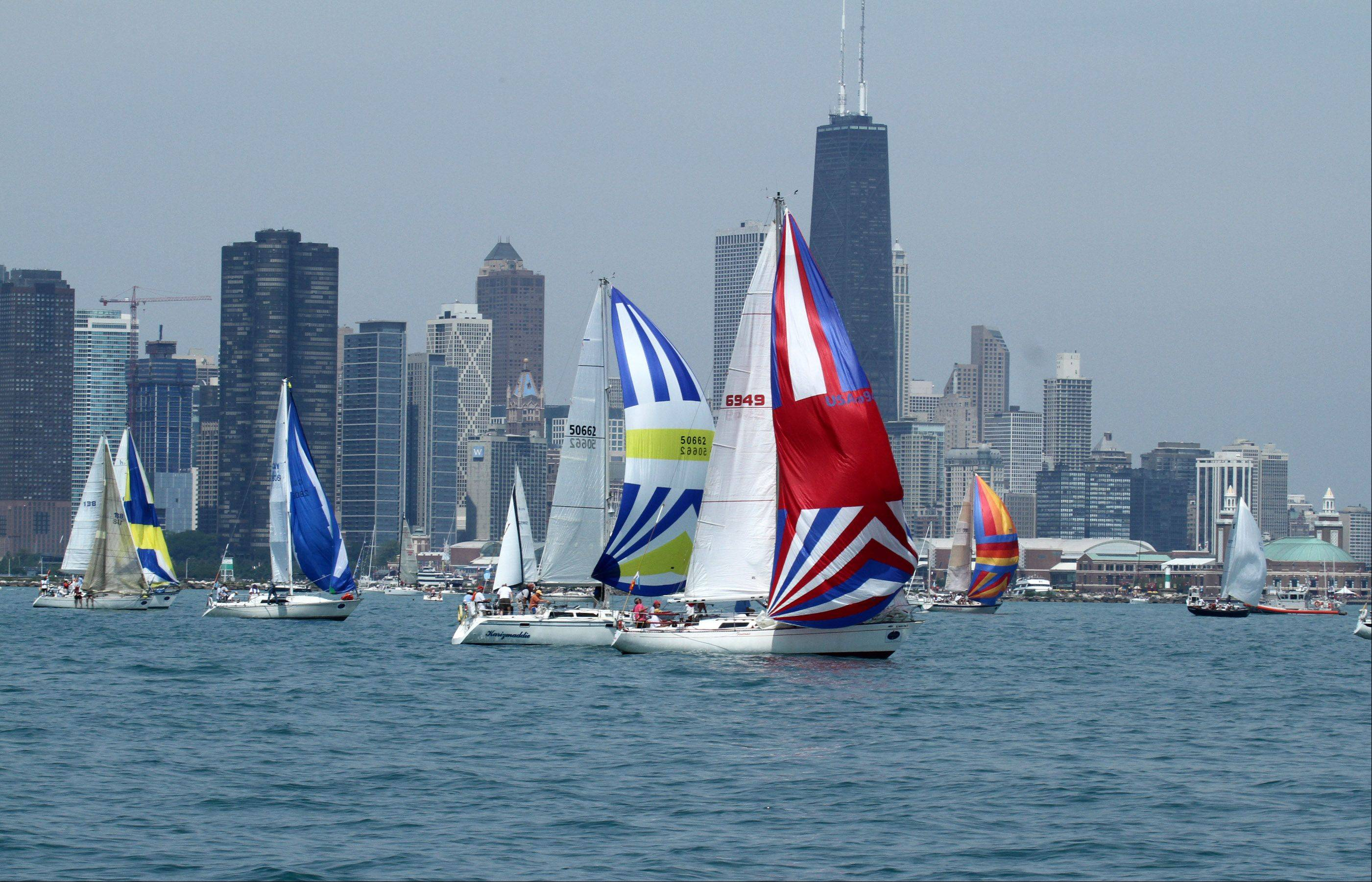 Sailboats lead by Fantome, right front, USA 6949, owned by Deirdre Martin, of Chicago, with Chicago Yacht Club, at the start of the 104th Chicago Yacht Club Race to Mackinac on Lake Michigan pass Navy Prier in Chicago on Saturday, July 21.