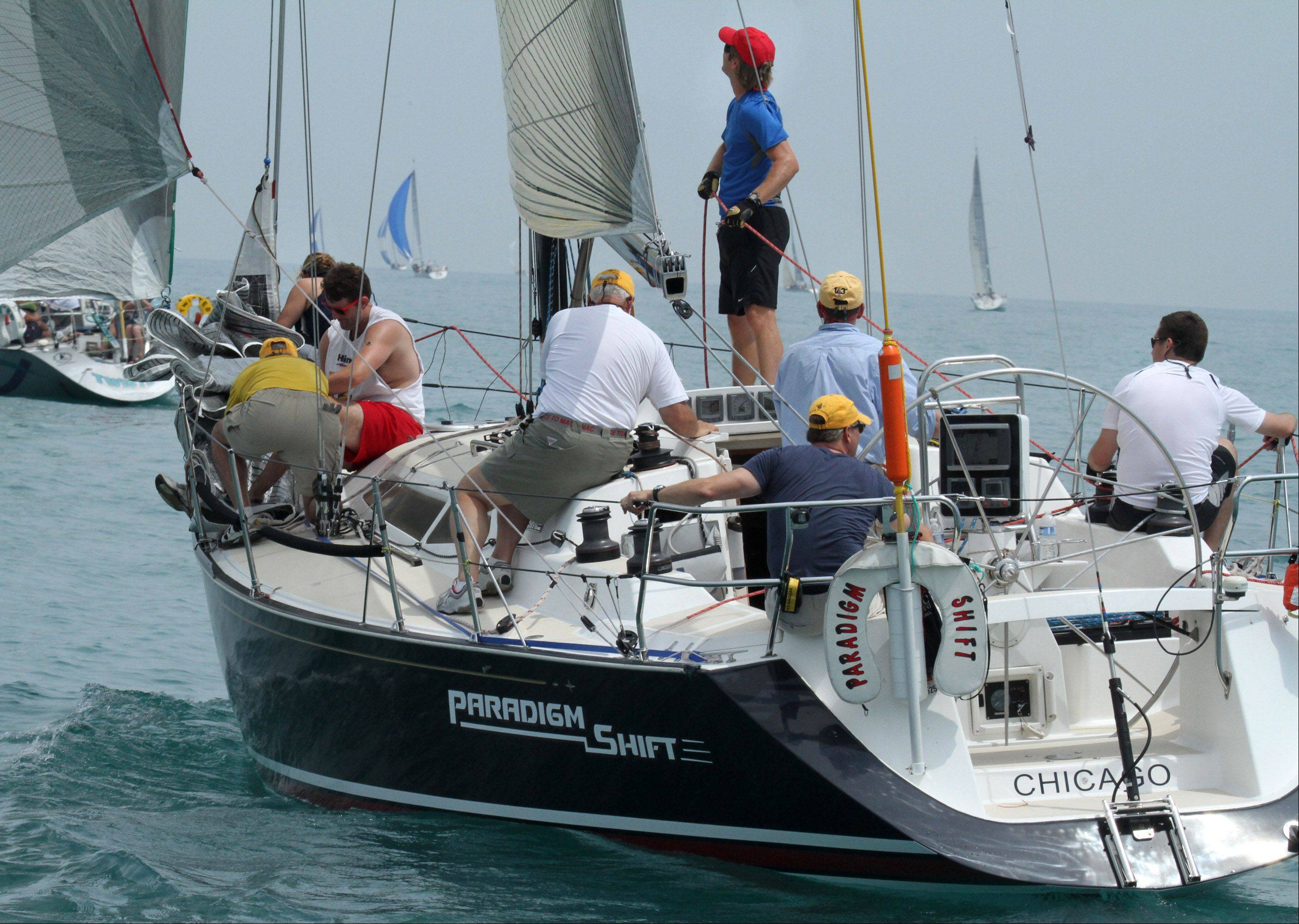 Crew members on board Paradigm Shift, USA 25578, owned by Dave Dickerson, Steve Daube, and John Brofman, of Hinsdale, with Chicago Yacht Club raise sail to start of the 104th Chicago Yacht Club Race to Mackinac on Lake Michigan near Chicago on Saturday, July 21.