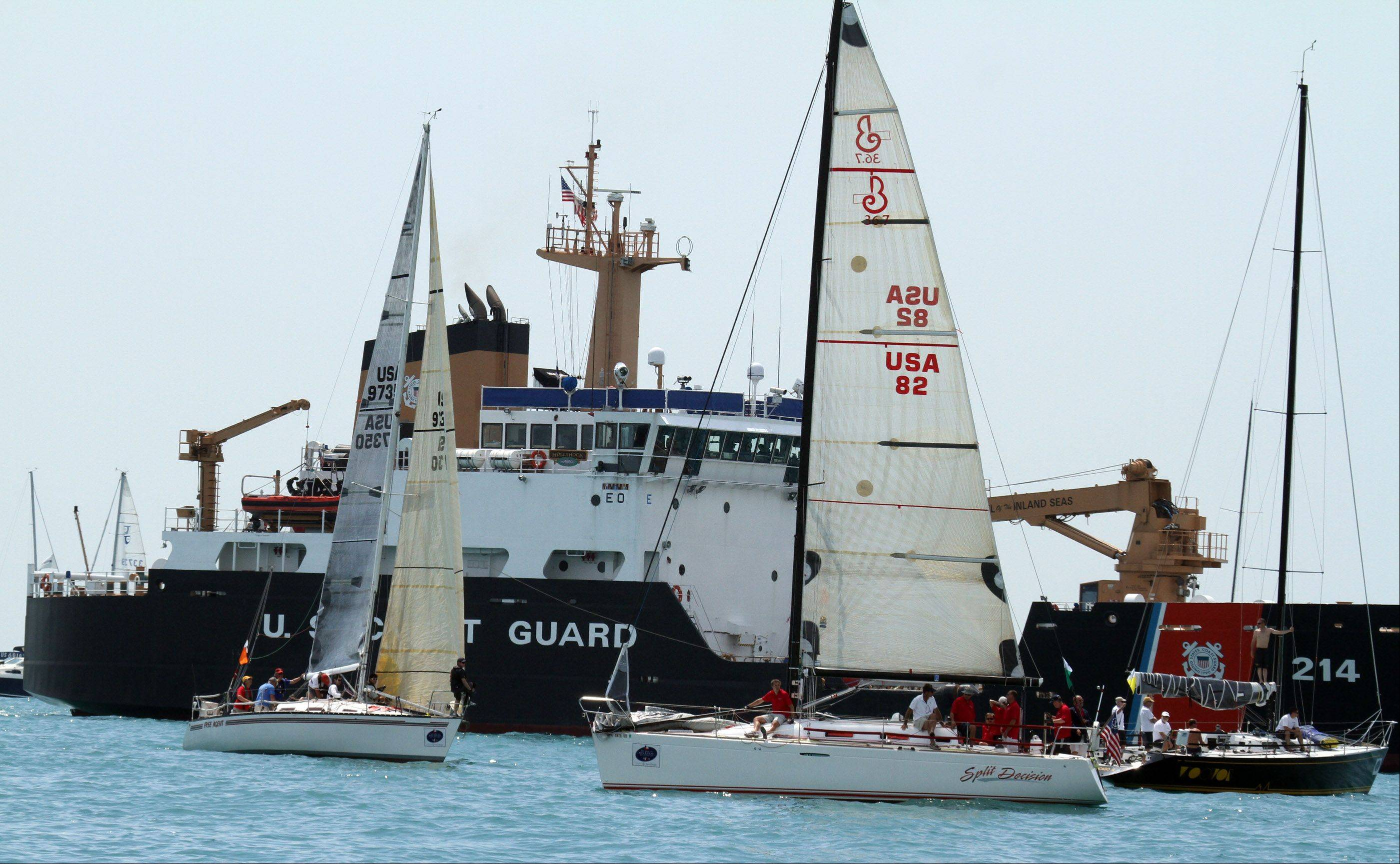 A U.S. Coast Guard ship was near Split Decision, right, USA 82, owned by Mark Norris, of Chicago, with the Chicago Yacht Club, just before the start of the 104th Chicago Yacht Club Race to Mackinac on Lake Michigan near Chicago on Saturday, July 21.