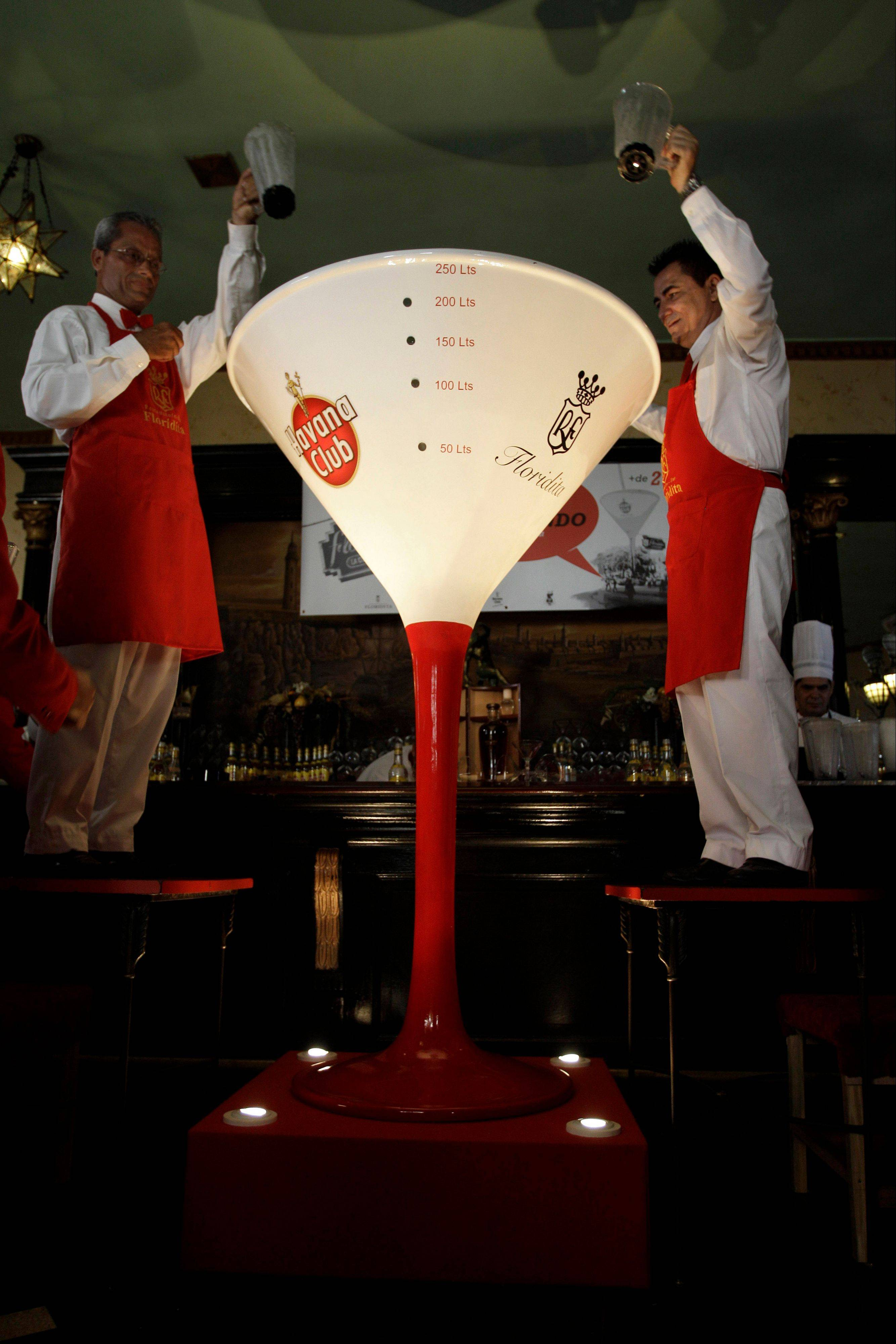 Standing on a wooden platform, Eduardo Bautista, right and Labrador Ahmed hold up empty pitchers Saturday after filling an oversized fiber-composite cocktail glass with daiquiris at El Floridita tavern in Old Havana, Cuba.