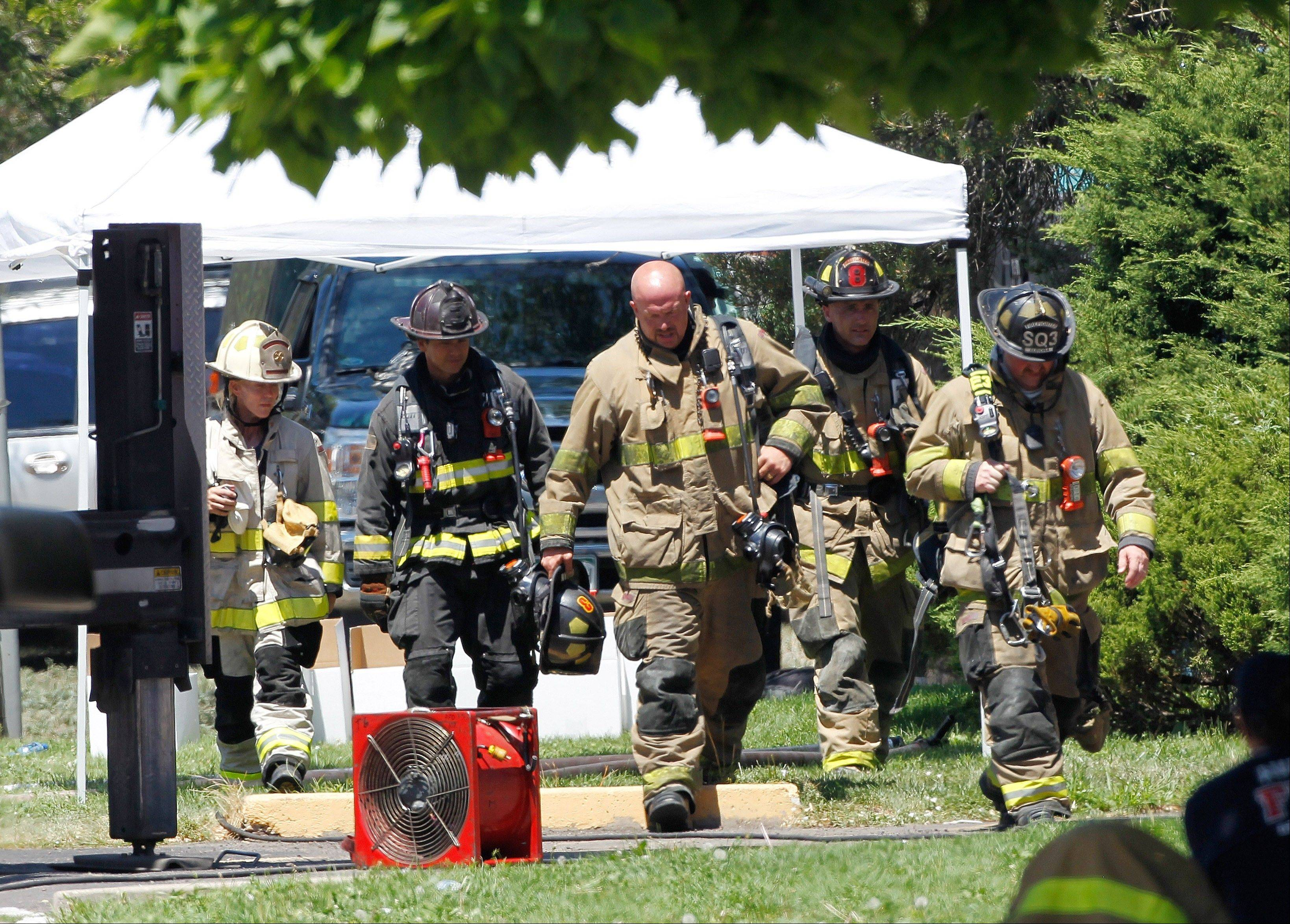 Firefighters walk to shade Saturday as temperatures neared 100 degrees, at the booby trapped apartment of James Eagen Holmes, who police have identified as the suspect in the deadly shooting at a crowded movie theater a day earlier.