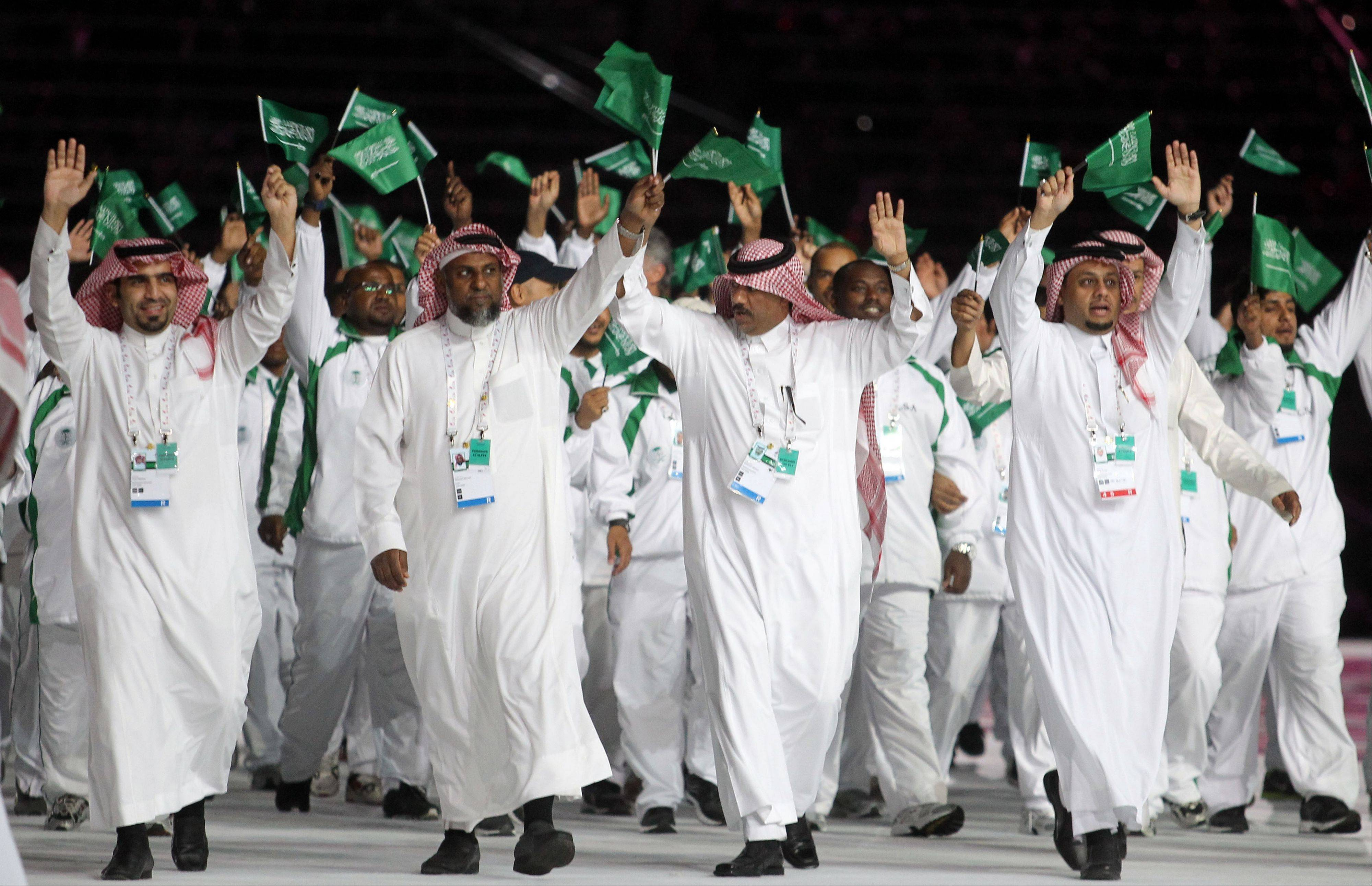 In this Friday, Dec. 9, 2011 file photo, members of Saudi Arabia team take part in the opening ceremony of the pan-Arab Games at Sheikh Khalifa stadium in the Qatari capital Doha. These Middle Eastern countries have also only embraced women's sports in the past decade, with Saudi Arabia and Qatar sending women to the Olympics for the first time this year.