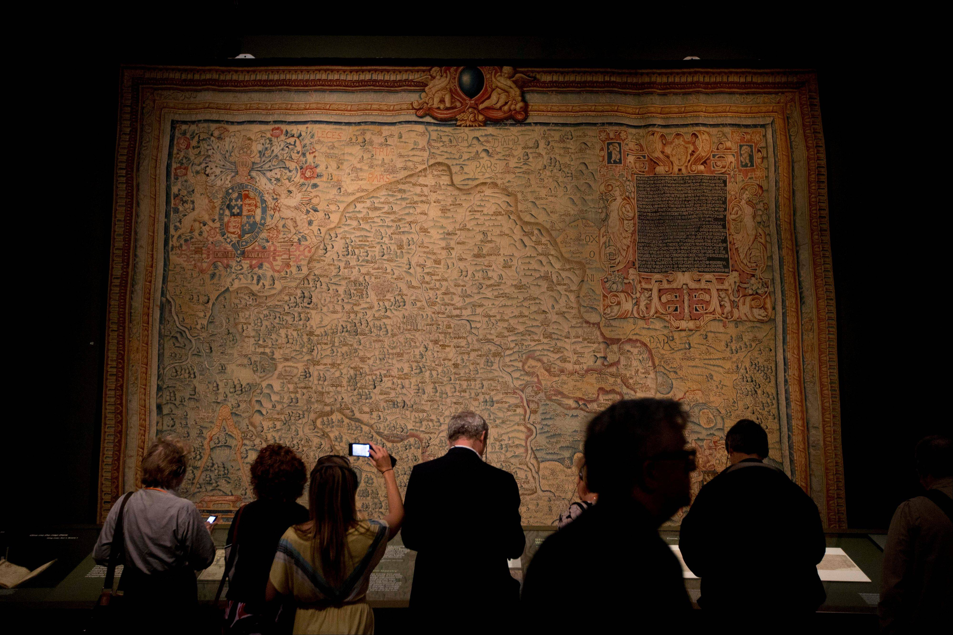 "People stand in front of a tapestry map of the county of Warwickshire, where Shakespeare was brought up, dated about 1588, made for wealthy landowner Ralph Sheldon, during the press view of the ""Shakespeare: staging the world"" exhibition at the British Museum in London, Wednesday, July 18, 2012. The exhibition, which is being held as part of the London 2012 cultural Olympiad, provides a unique insight into the emerging role of London as a world city 400 years ago, seen through the innovative perspective of Shakespeare's plays. It runs from July 19 to November 25."