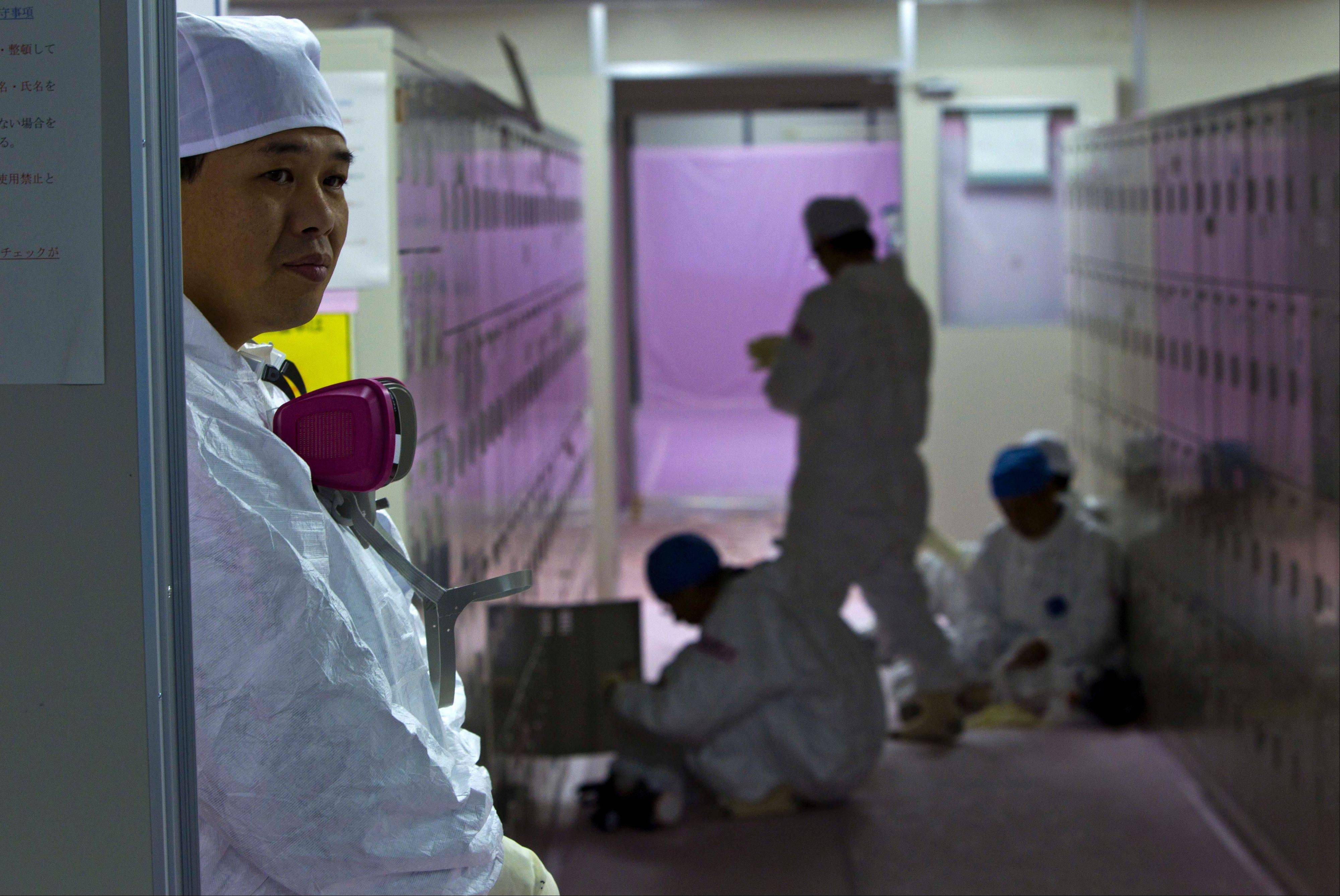 In this Nov. 12, 2011, file photo, workers in protective suits gather near their lockers inside the emergency operation center at the crippled Fukushima Dai-ichi nuclear power station in Okuma, Japan. Japanese labor officials said Sunday they are investigating subcontractors on suspicion they forced workers at the tsunami-hit nuclear plant to underreport their dosimeter readings so they could stay on the job longer.