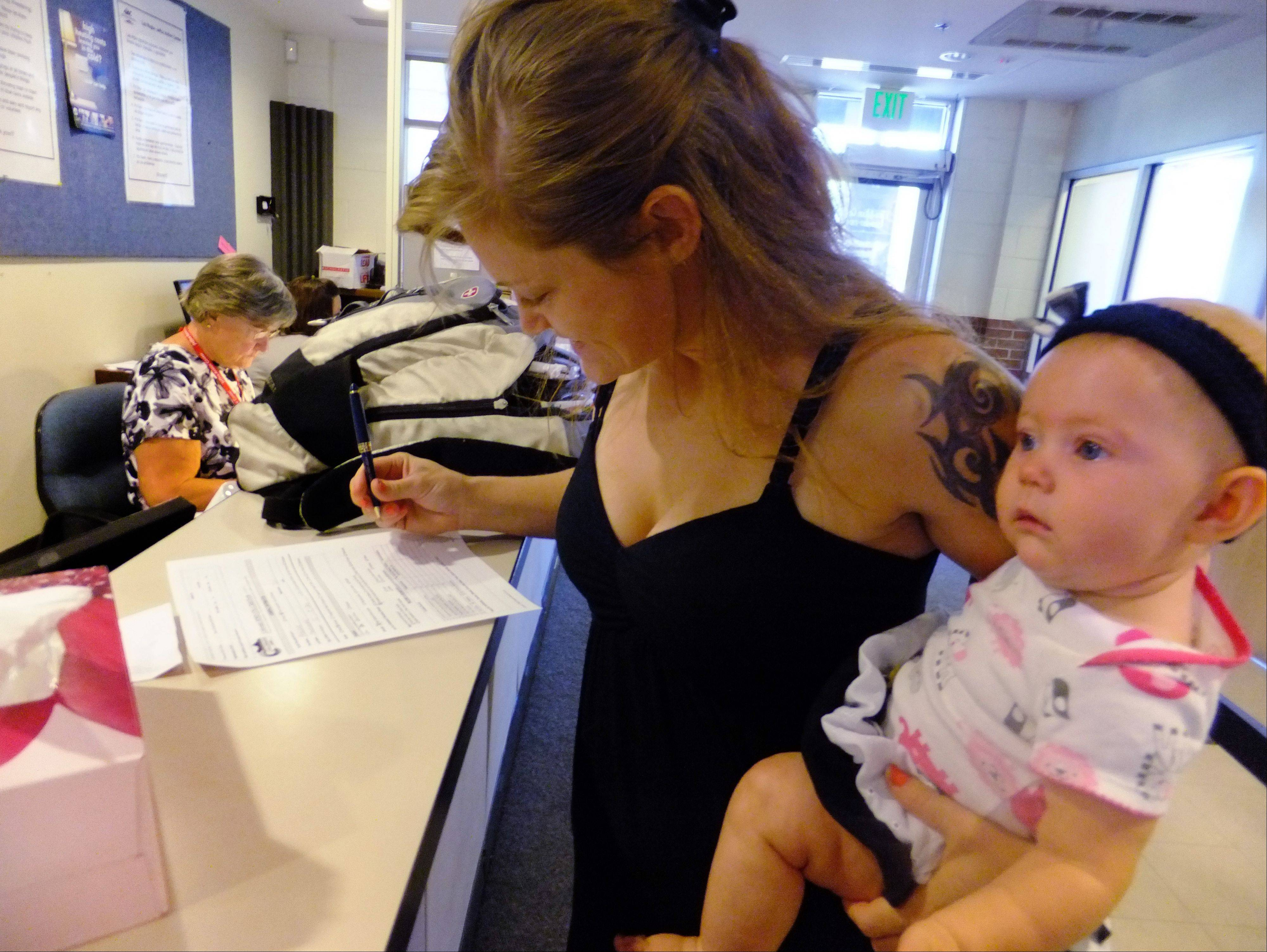Laura Fritz, 27, left, with her daughter, Adalade Goudeseune, fills out a form at the Jefferson Action Center, an assistance center in the Denver suburb of Lakewood. Fritz grew up in the Denver suburbs, a solidly middle class family, but she and her boyfriend, who has struggled to find work, and are now relying on government assistance to cover food and $650 rent for their family.