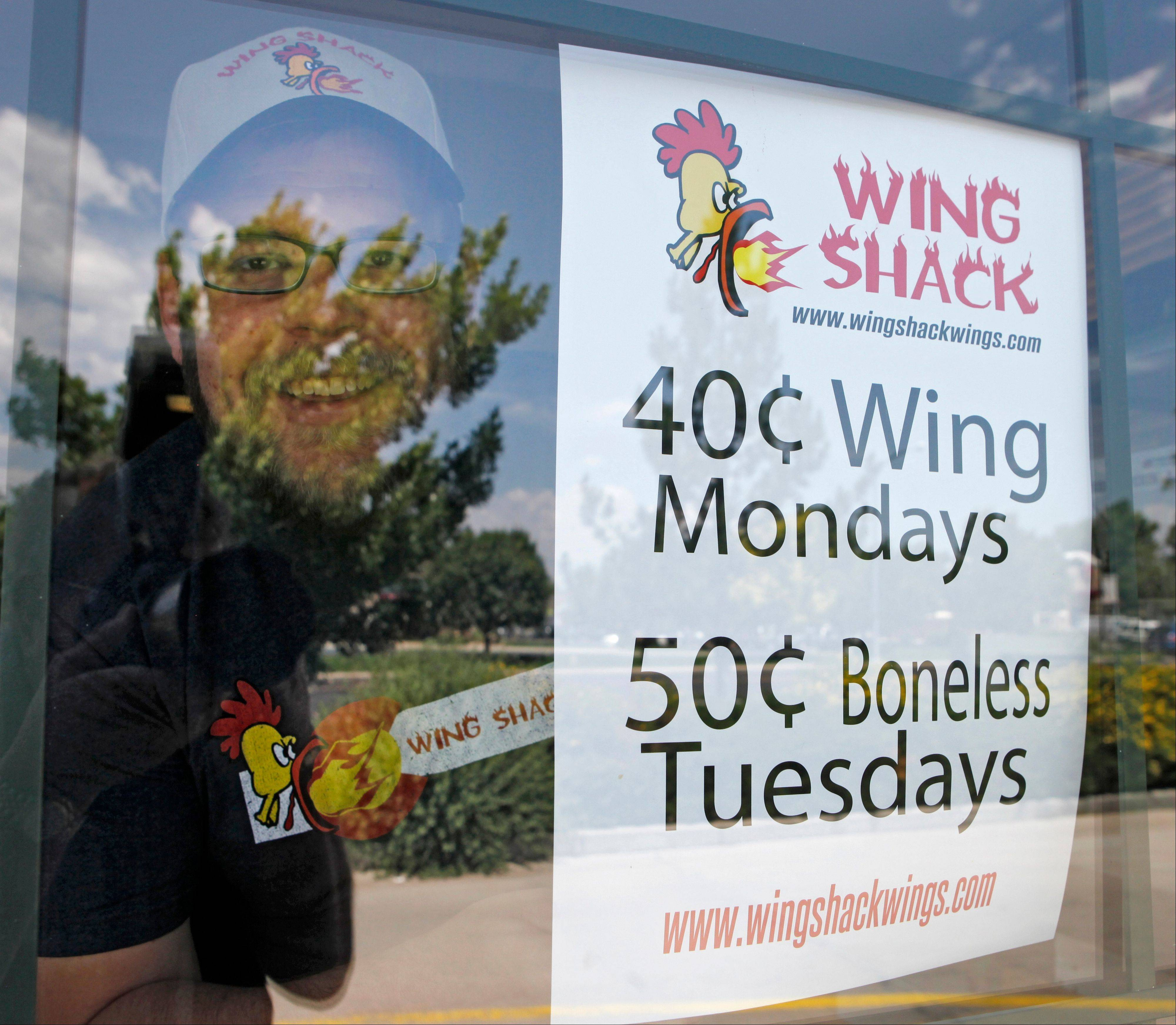 Brian Seifried, owner of the Wing Shack, stands next to a sign advertising special prices at his new restaurant in Windsor, Colo. Seifried was just 20 when he opened a hole-in-the wall chicken wing shack eight years ago in Greeley. He expanded during the recession and in June 2012, opened his fourth place in a 30-mile range. �There were times when I was self-conscious talking to neighbors and fellow business owners,� he says. �I kind of played down our success just not to come across as bragging.� Politically, Seifried says he agrees with the president�s position that the top 1 percent should contribute more taxes, but �I don�t feel the federal government is efficient with the money that they do bring in. ... I�m only 28. In consider myself socially liberal �, but I don�t think Democrat or Republican is the answer.� (AP Photo/Ed Andrieski)