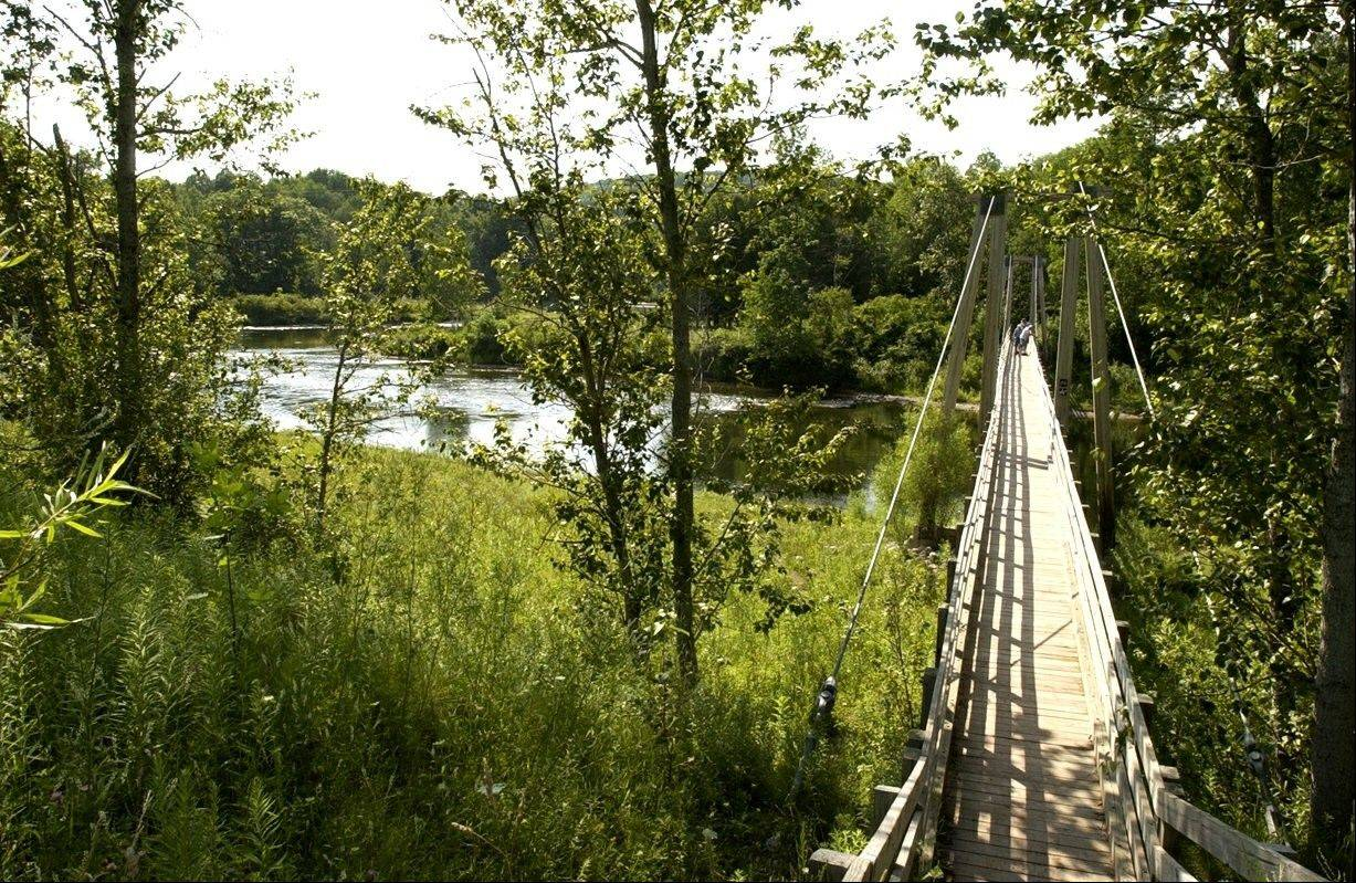 A suspension bridge over the Manistee River southeast of Mesick, Mich., where the North Country Scenic Trail follows the river for miles. Closing the 40-mile gap is a priority for the Michigan-based North Country Trail Association, the group responsible for the trail.