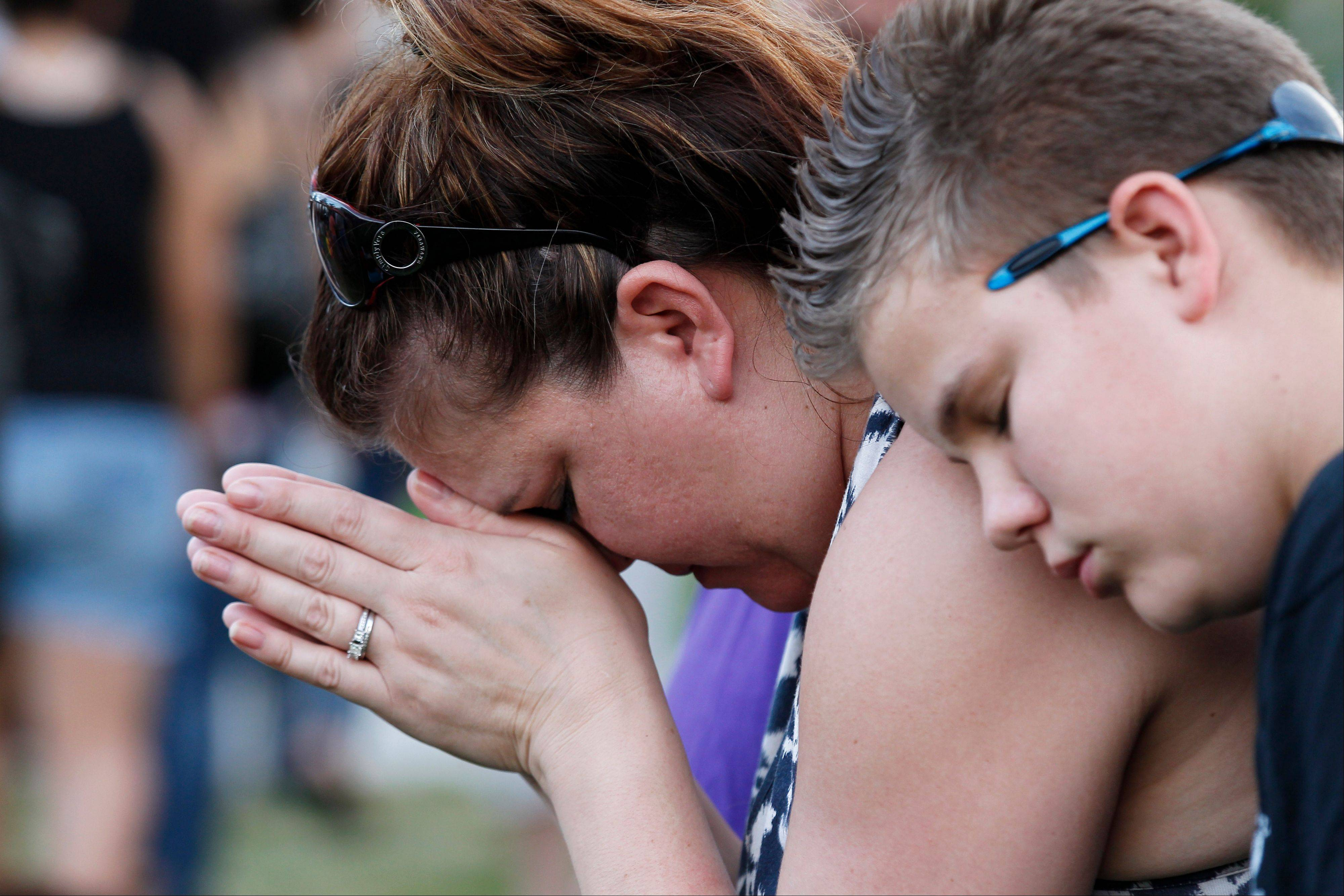 Dylan Bowen, 13, right, holds onto his mother Lorri Hastings as they pray Sunday in Aurora, Colo., during a prayer vigil for the victims of Friday's mass shooting at a movie theater.
