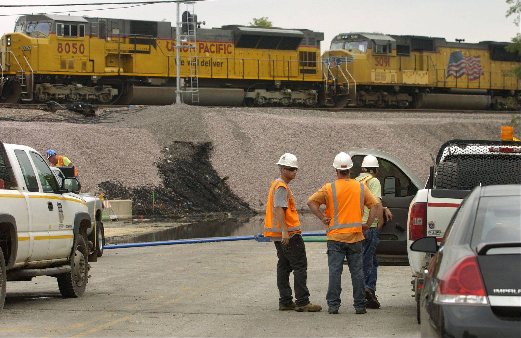 A train passes over Shermer Road while the Glenview train derailment cleanup continues.