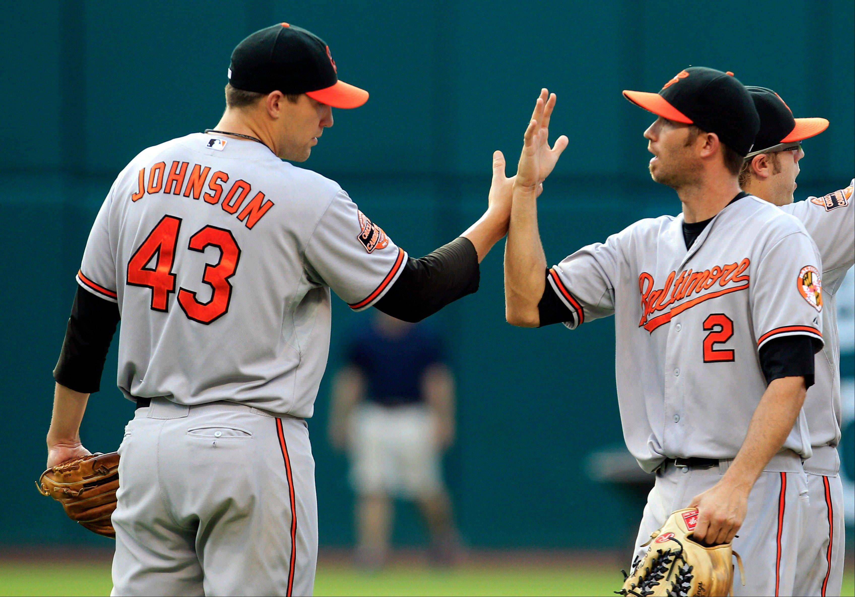 Baltimore closer Jim Johnson, left, congratulates J.J. Hardy after the Orioles defeated the Indians 4-3 Sunday in Cleveland.