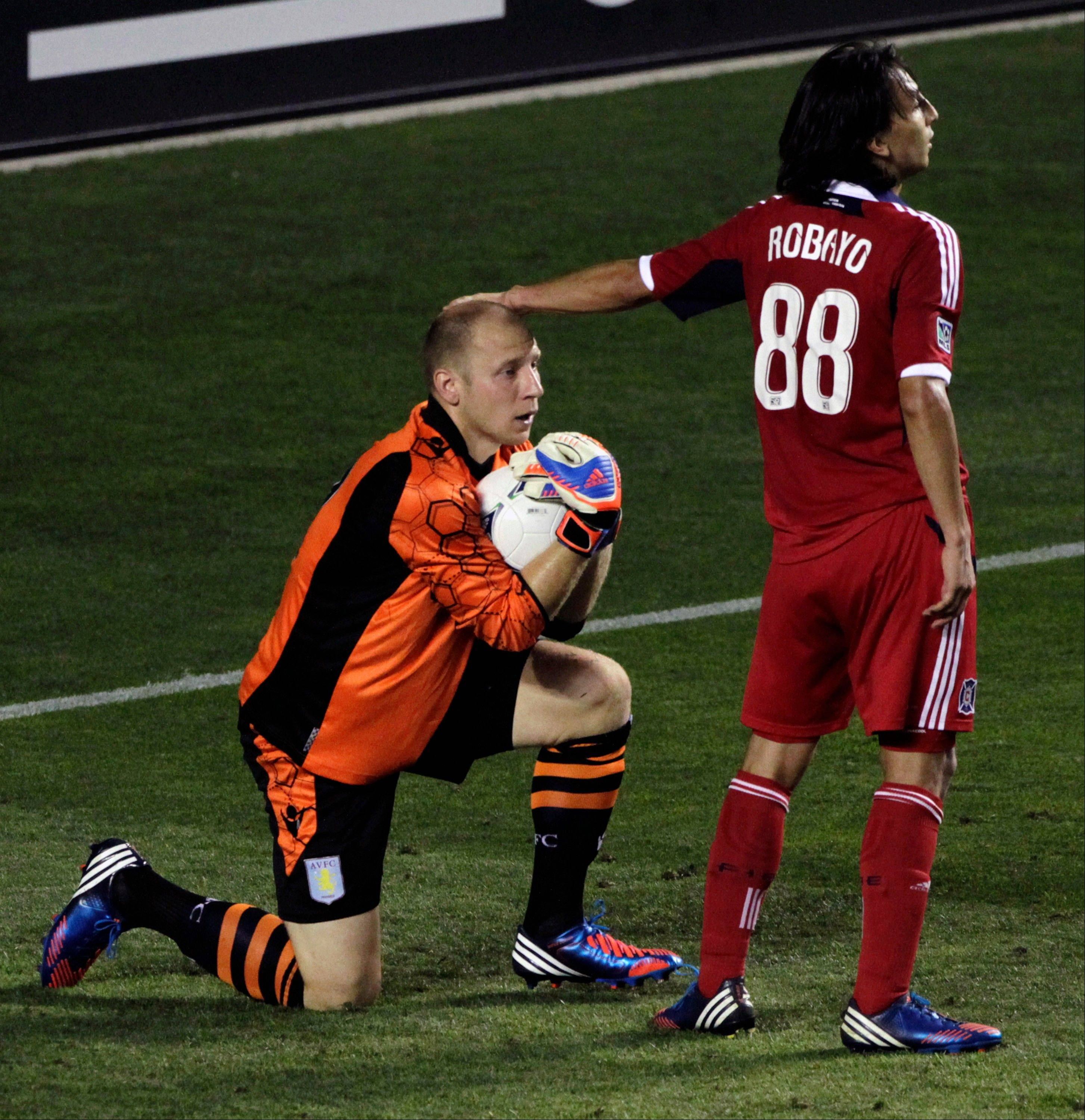 Aston Villa�s goalie Brad Guzan, left, gets a pat the head by Chicago Fire�s Rafael Robayo after making a last-second save during the second half of a friendly soccer game on Saturday, July 21, 2012, at Toyota Park in Bridgeview, Ill. Aston Villa won 1-0.
