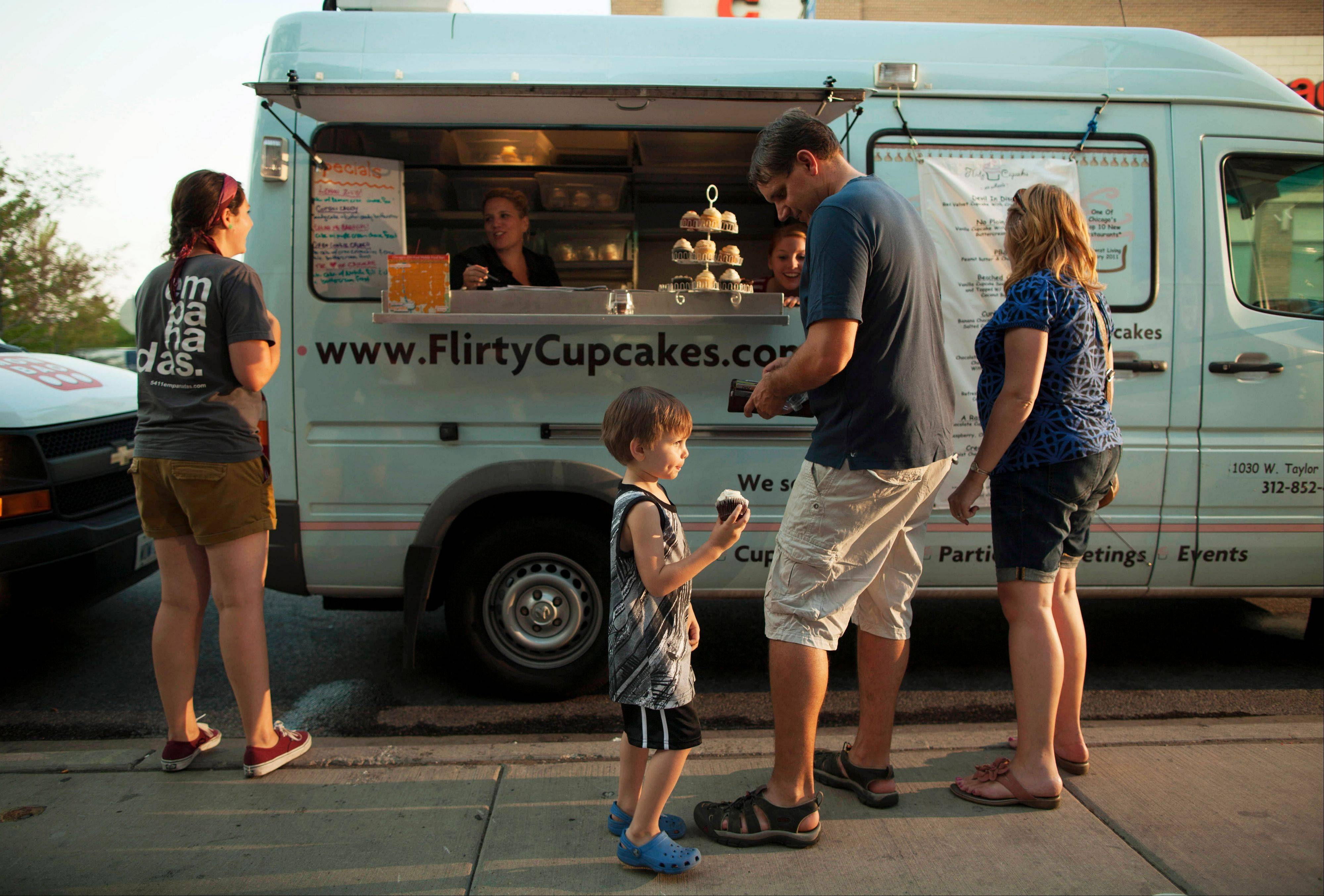 In this July 12, 2012 photo, a young customer eats a cupcake bought from the Flirty Cupcakes food truck in Chicago. A proposed ordinance would finally allow food trucks to cook and prepare food but continue to ban them from setting up shop any closer than 200 feet away from restaurants and capping the time they can stay put in one spot at two hours. The full City Council could vote on the proposal as soon as next week.