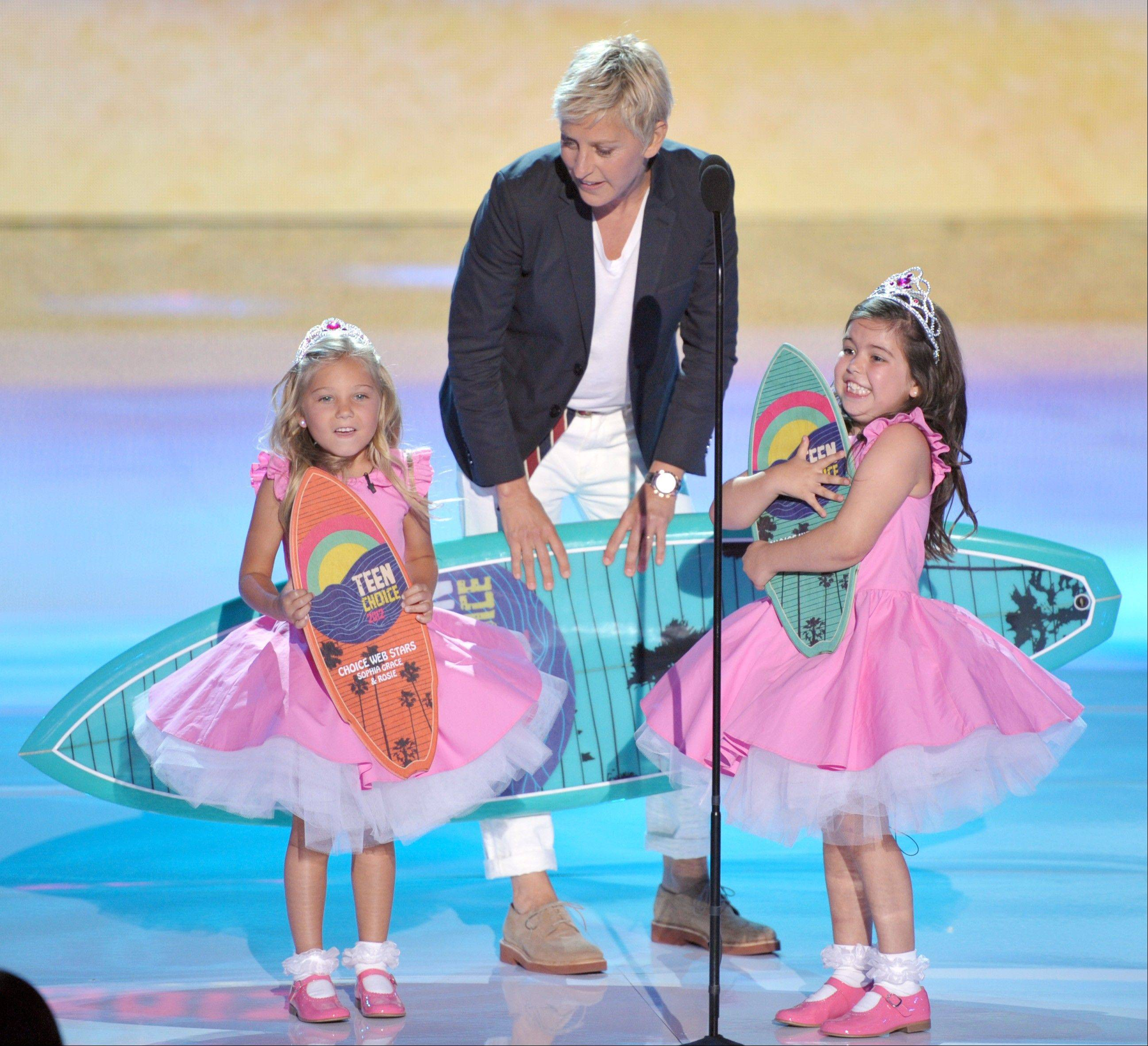 Ellen DeGeneres, center, accepts the award for choice comedian onstage with Rosie Mcclelland, left, and Sophia Grace Brownlee at the Teen Choice Awards on Sunday in Universal City, Calif.