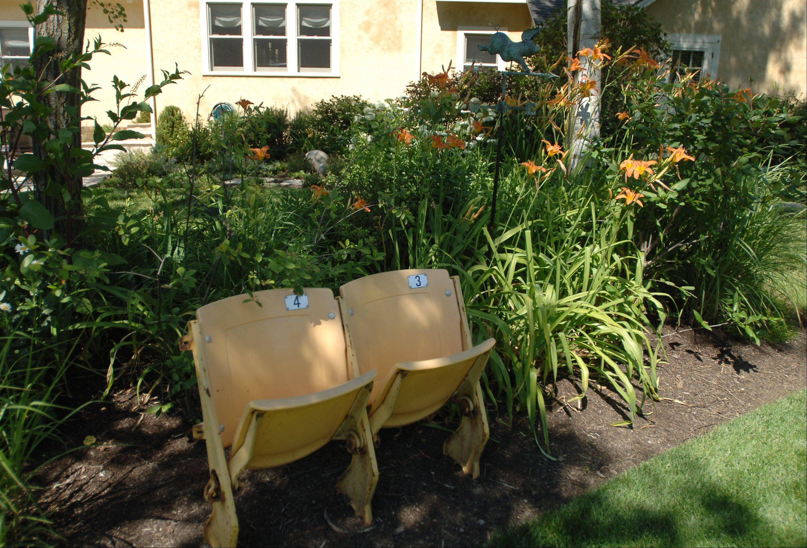 Two old seats from Soldier Field sit in Susan Brunstrum's garden.