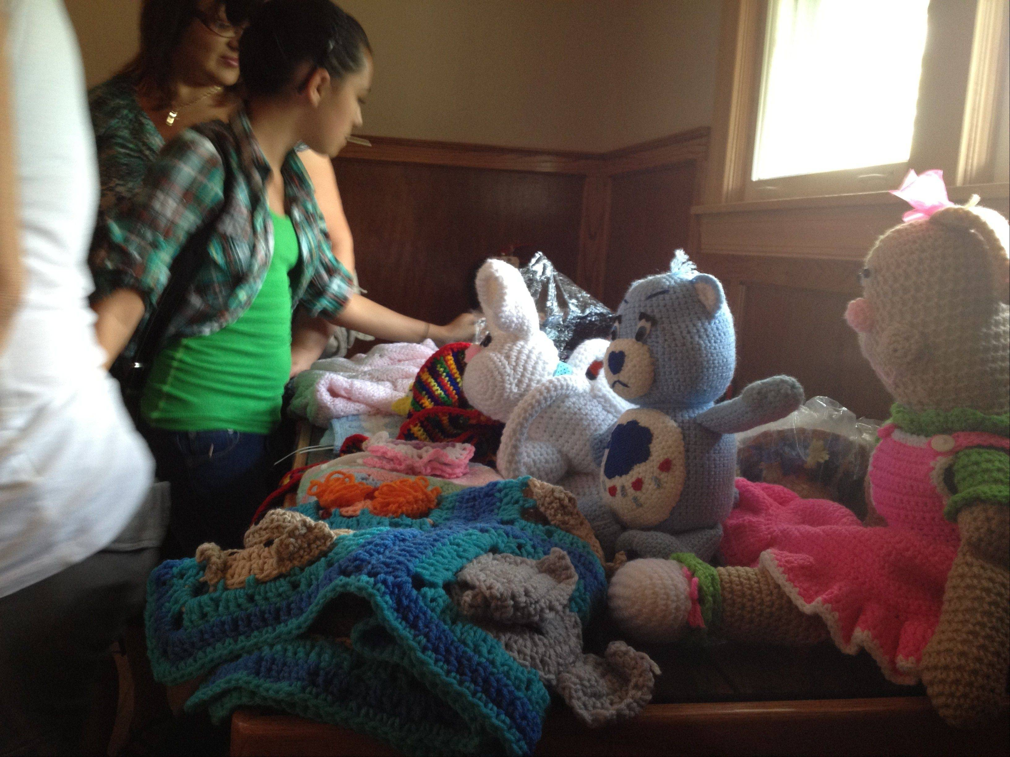 Nathan Saavedra's aunt and cousin, Michelle and Pamela Bridges, sold blankets, hats and toys they knitted for the fundraiser Sunday at Lynfred Winery in Wheeling.