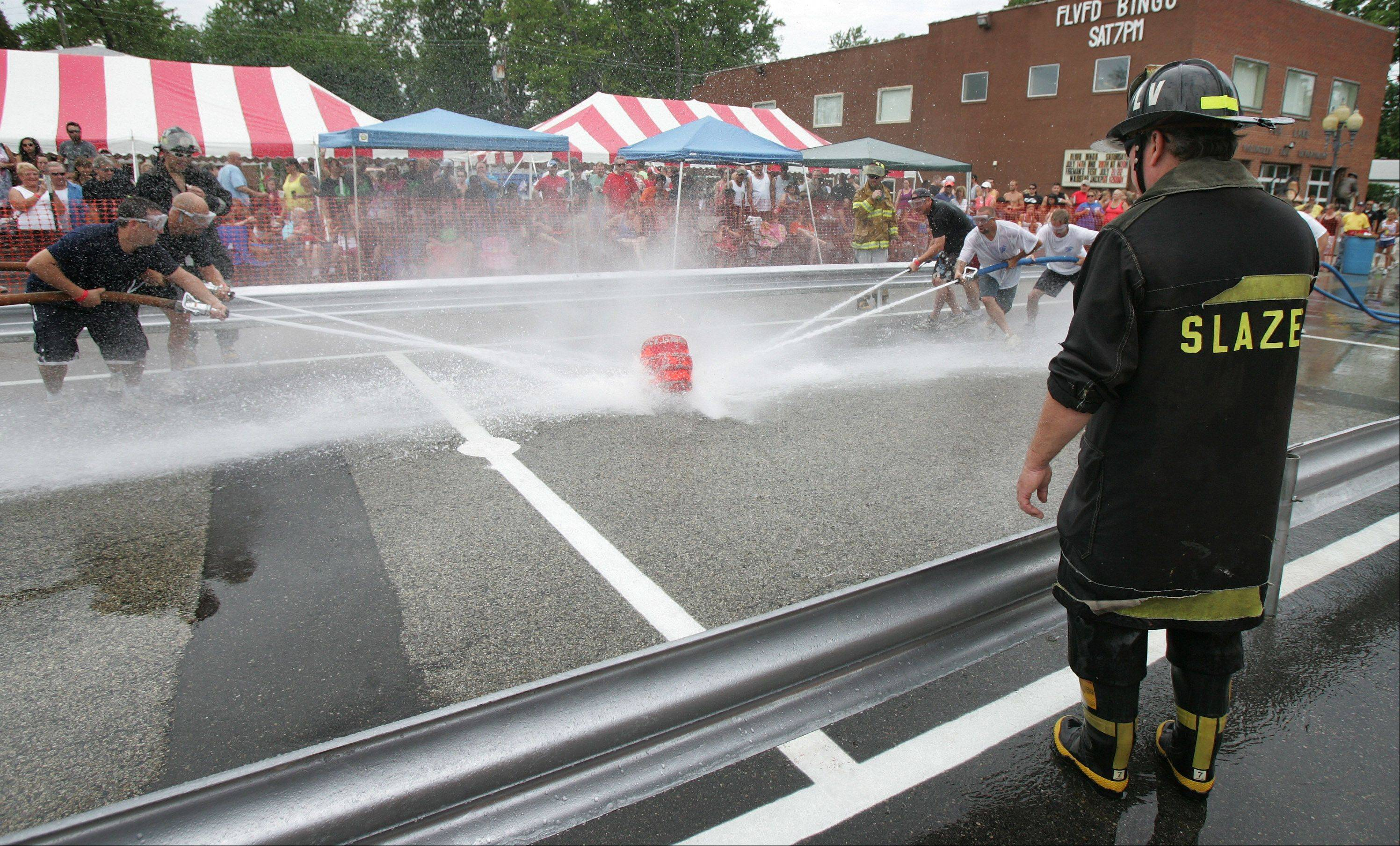 Lake Villa Fire Chief Frank Slazes, right, judges the battle between Team Chain Crawl and Team Merlins during the water fights at the Fox Lake Fireman's Festival Sunday near the Fox Lake bingo hall.