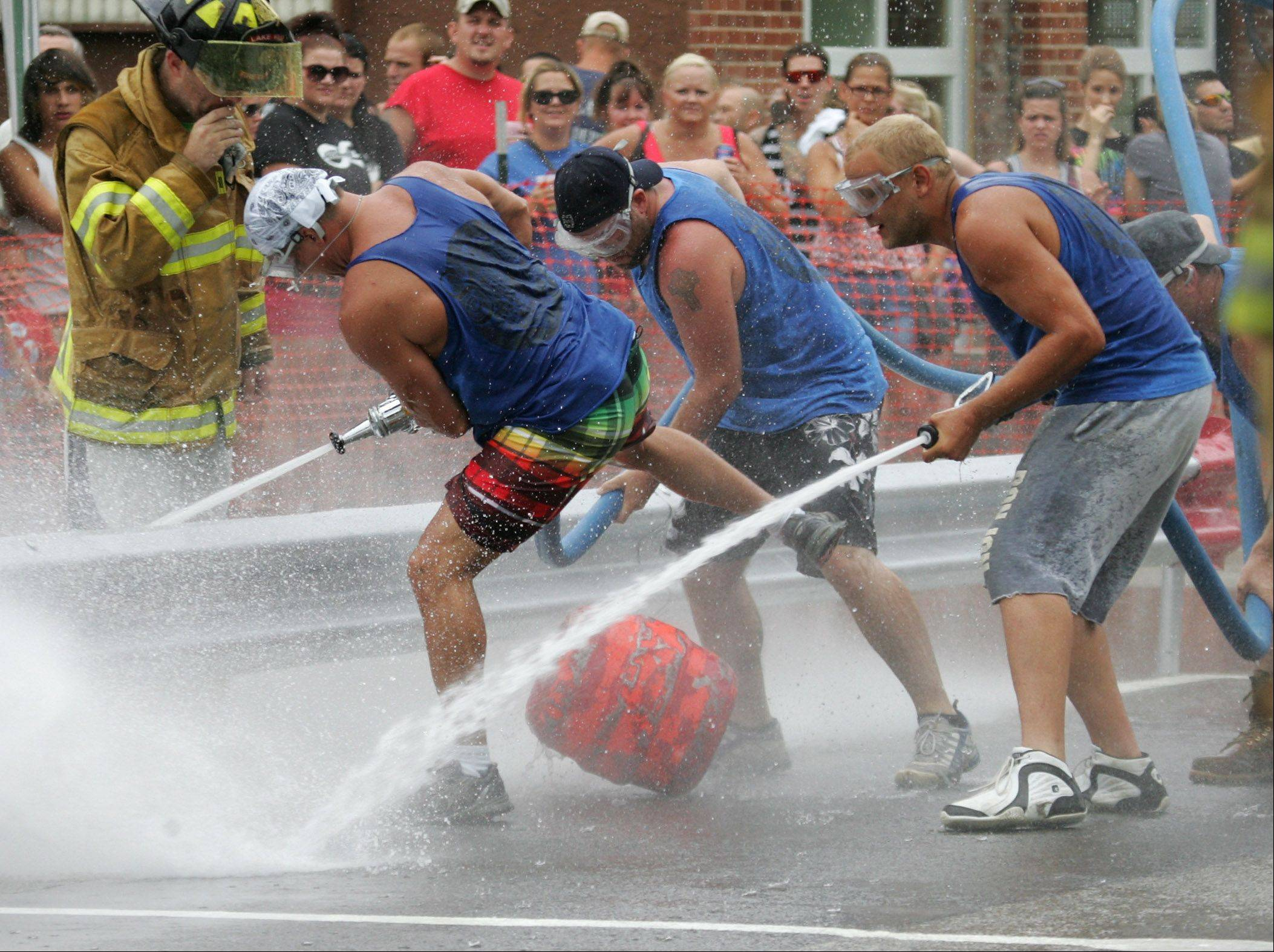 Bryan Bosack, left, and the rest of the Squad 2 team jump out of the way as the barrel goes shooting underneath them during the water fights Sunday at the 54th annual Fox Lake Fireman's Festival.