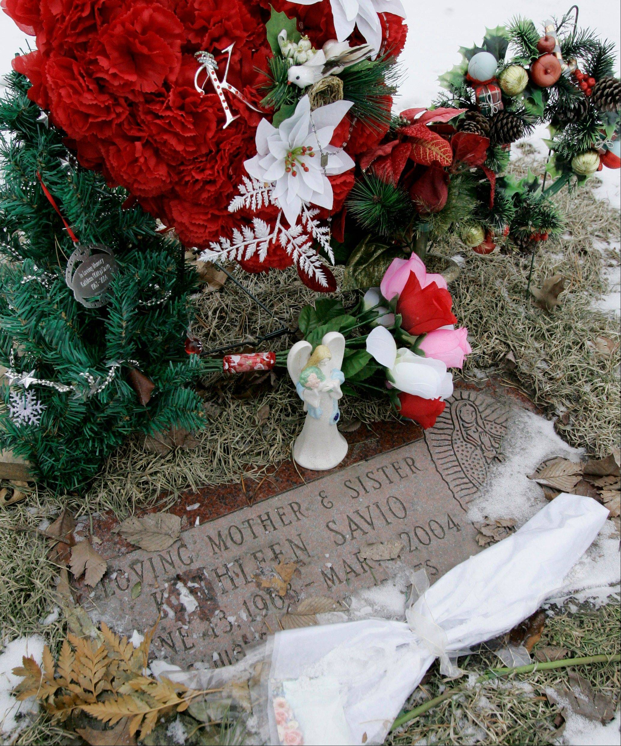 Flowers and a small angel statue surround the grave marker of Kathleen Savio, the third wife of Drew Peterson, at the Queen of Heaven Cemetery in Hillside on Feb. 22, 2008.