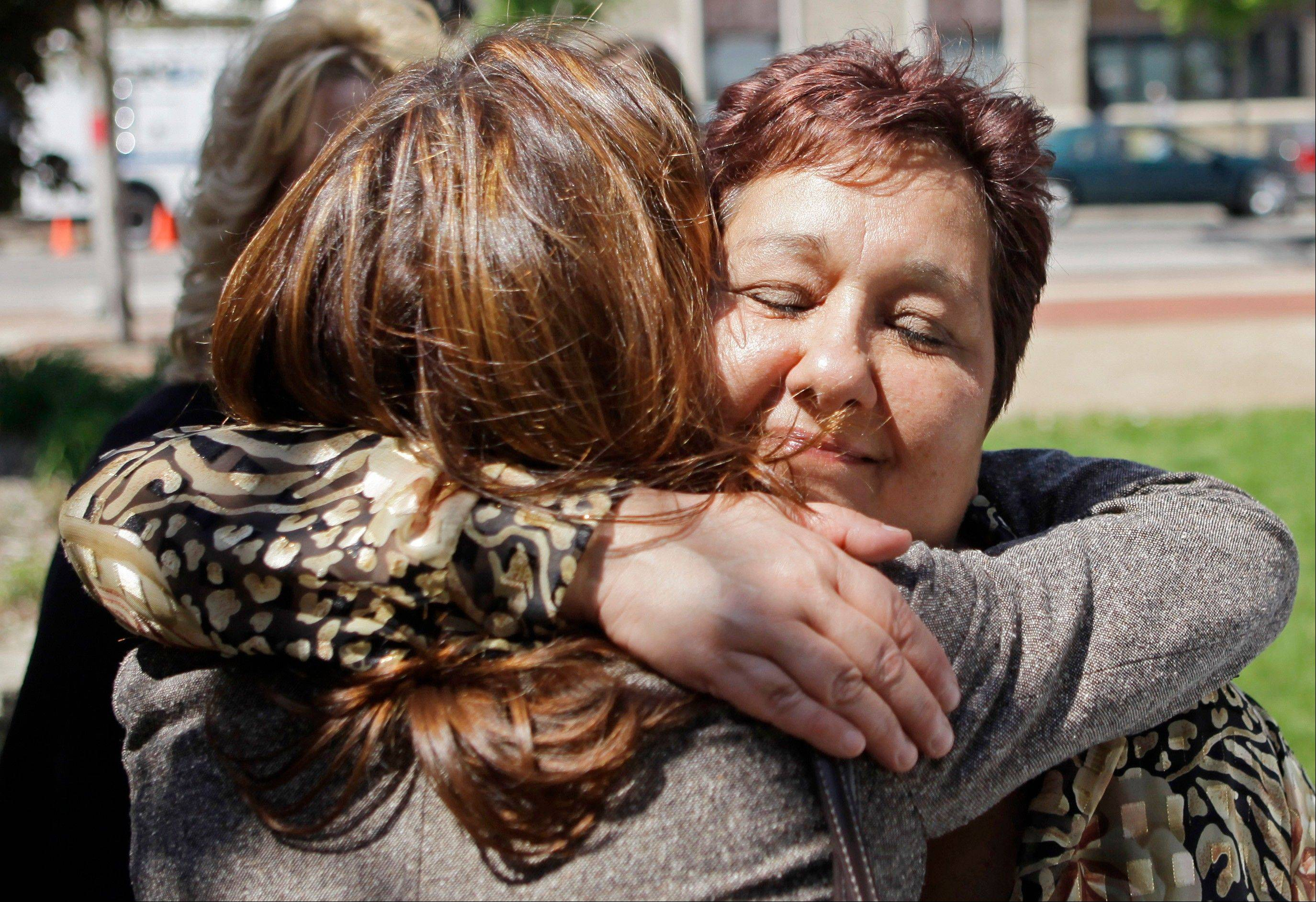 Susan Doman, right, sister of Kathleen Savio, gets a hug outside the Will County courthouse after a May 22, 2009, bond hearing where a judge refused to reduce former Drew Peterson's $20 million bail.
