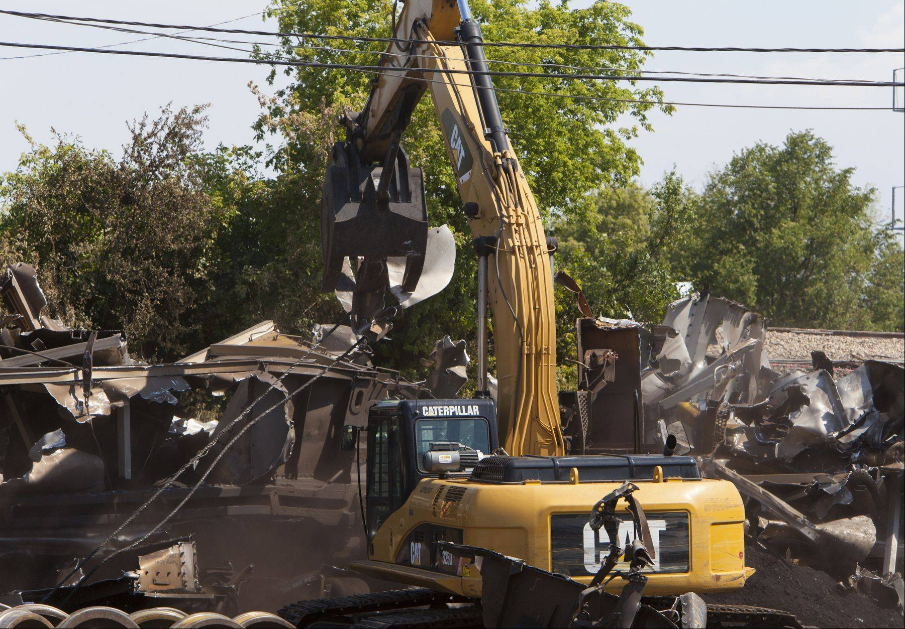 Union Pacific workers clean up train debris after a railroad bridge collapsed onto Shermer Road in Glenview, killing Zorine and Burt Lindner.