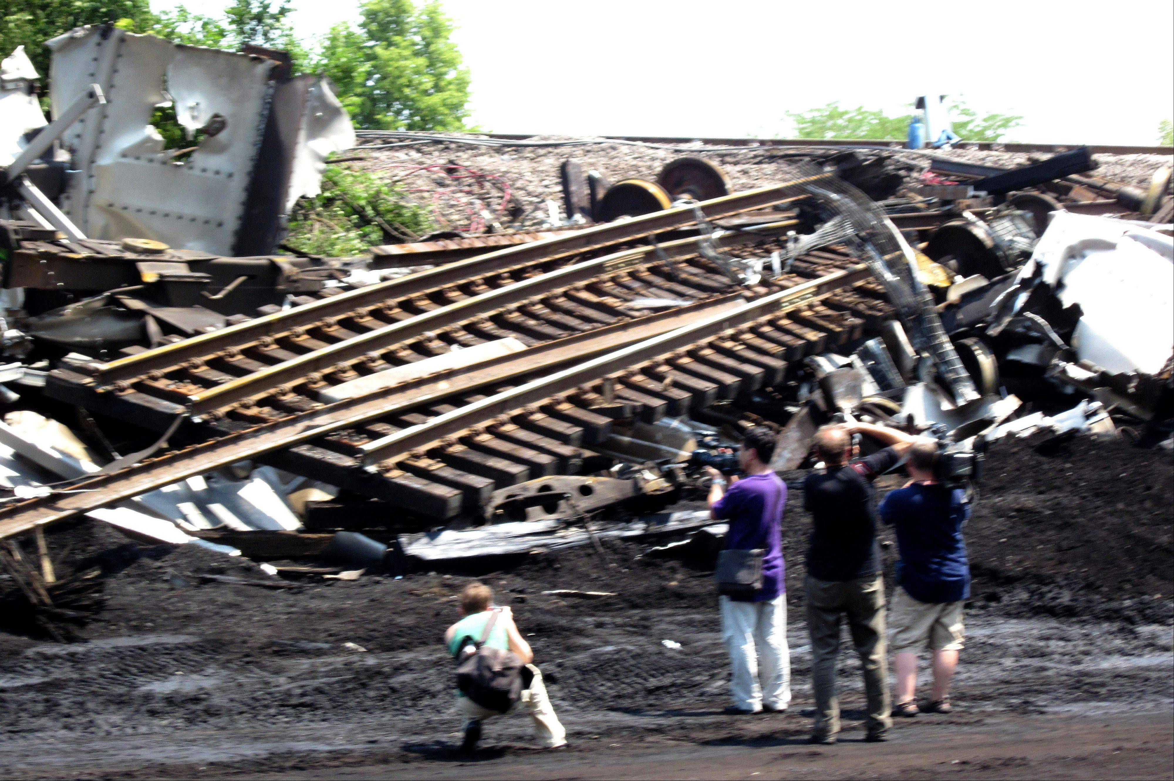News reporters and photographers record the scene of the train derailment near Glenview.