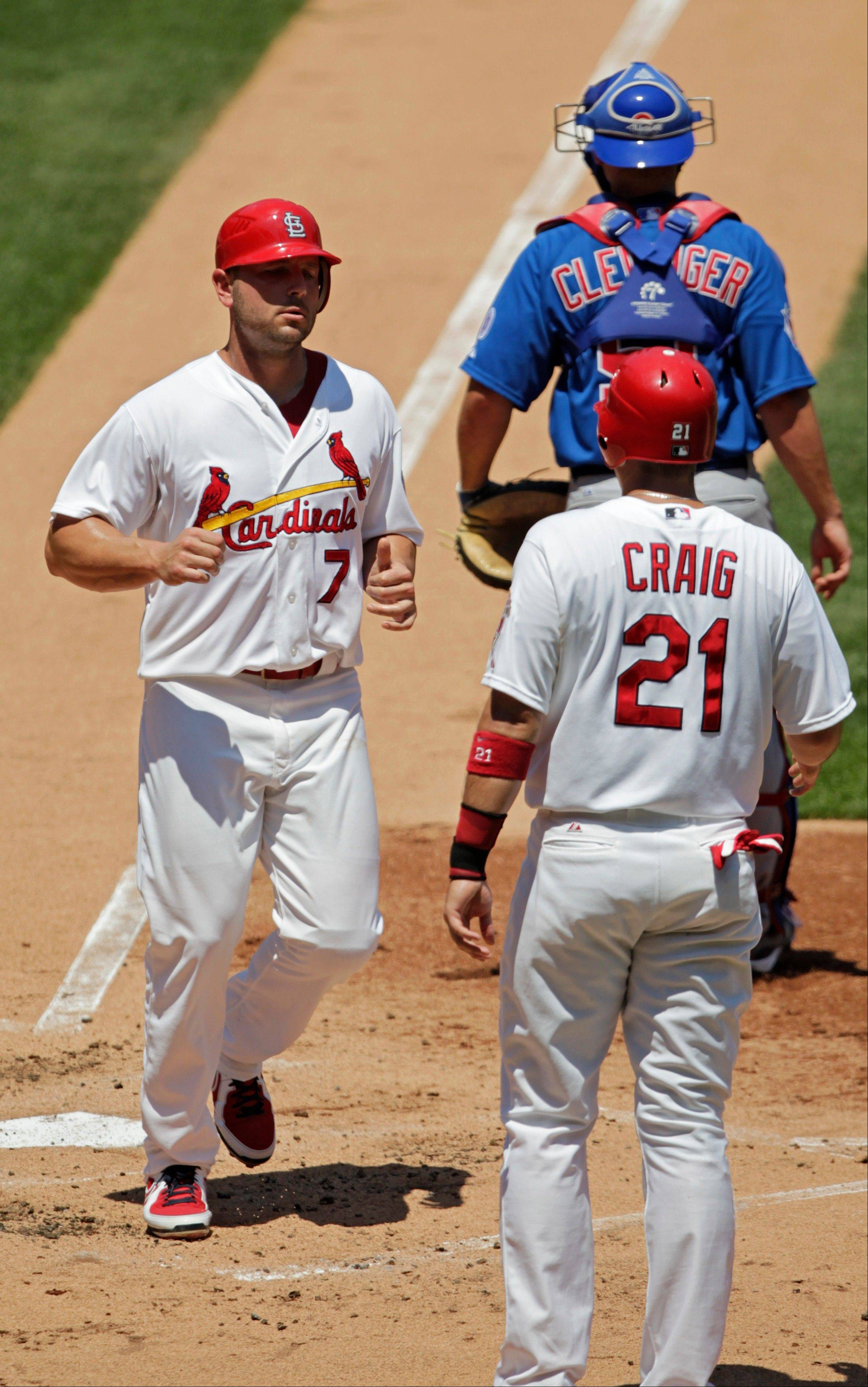 The St. Louis Cardinals' Matt Holliday (7) crosses home plate after scoring with Allen Craig on a double by Jon Jay as Cubs catcher Steve Clevenger looks for a throw in Sunday's first inning.