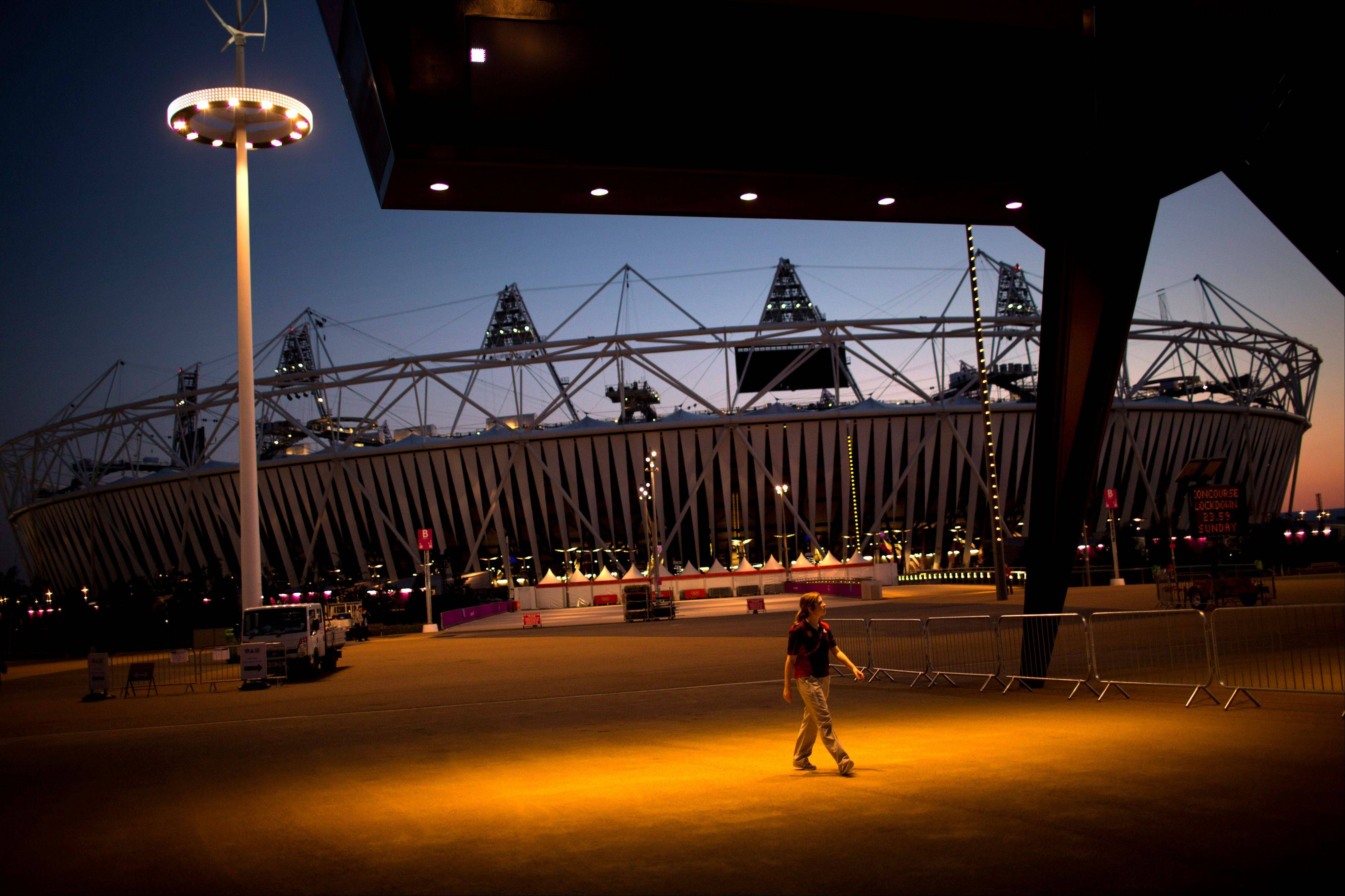 A volunteer walks past the Olympic Stadium at the 2012 Summer Olympics in London. The opening ceremonies of the Olympic Games are scheduled for Friday.