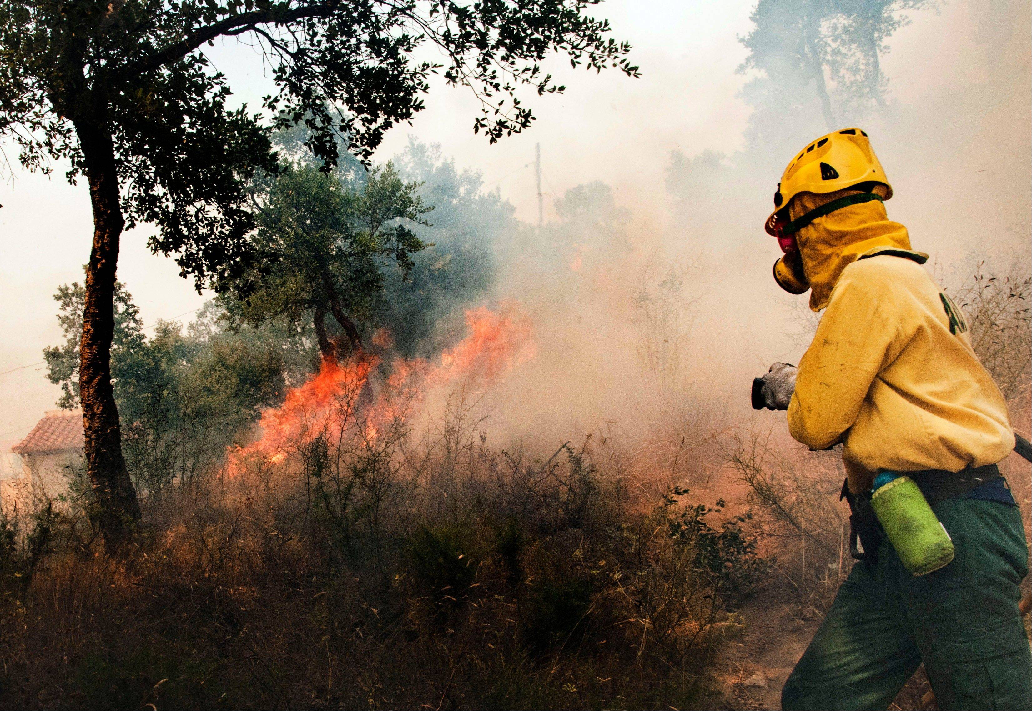 A firefighter tries to extinguish a wildfire by a house in La Jonquera, near the border with France, Spain, Sunday.
