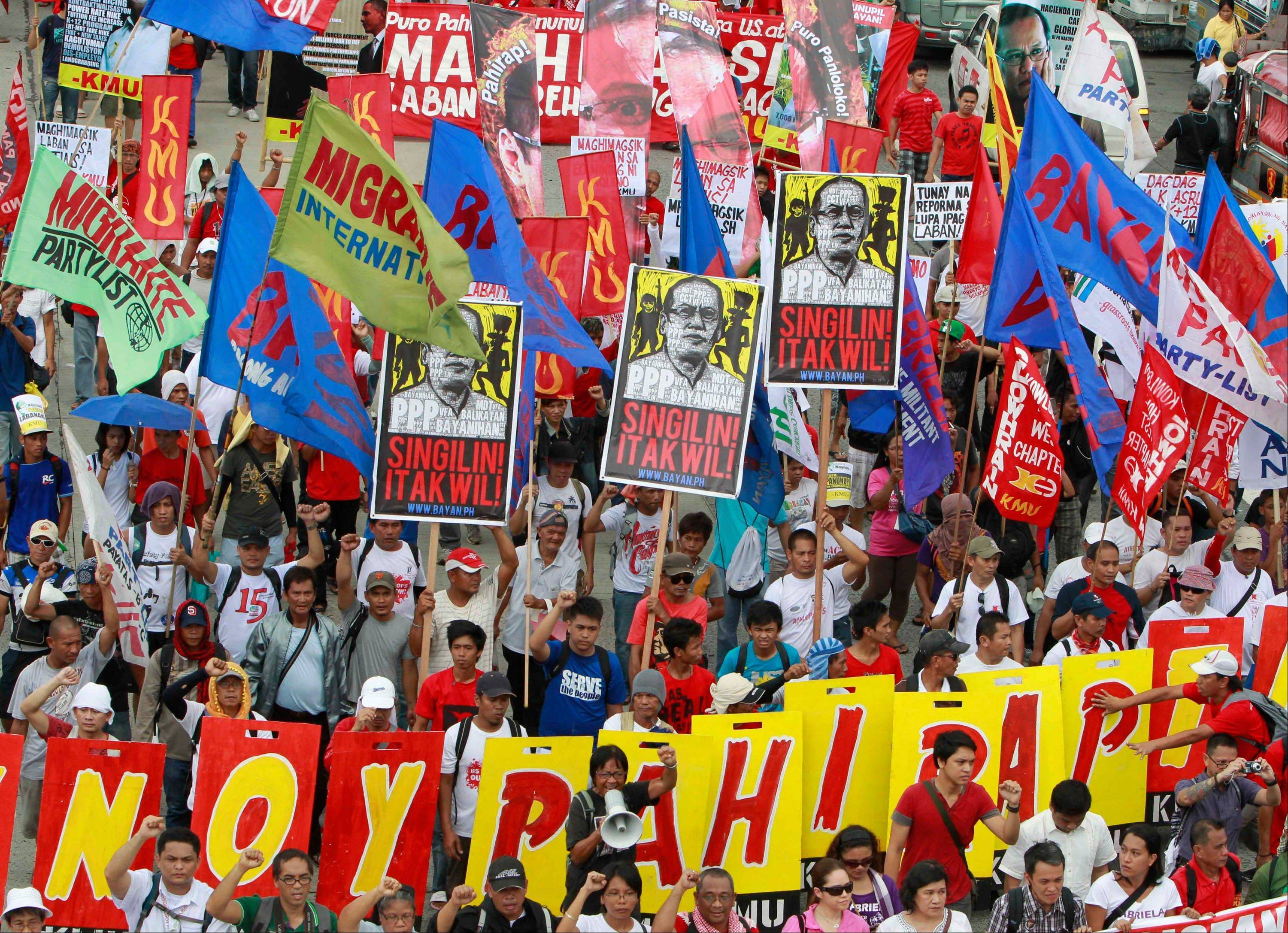Hundreds of protesters march toward the Philippine Congress to coincide with the third State of the Nation address of Philippine President Benigno Aquino III Monday, northeast of Manila, Philippines.