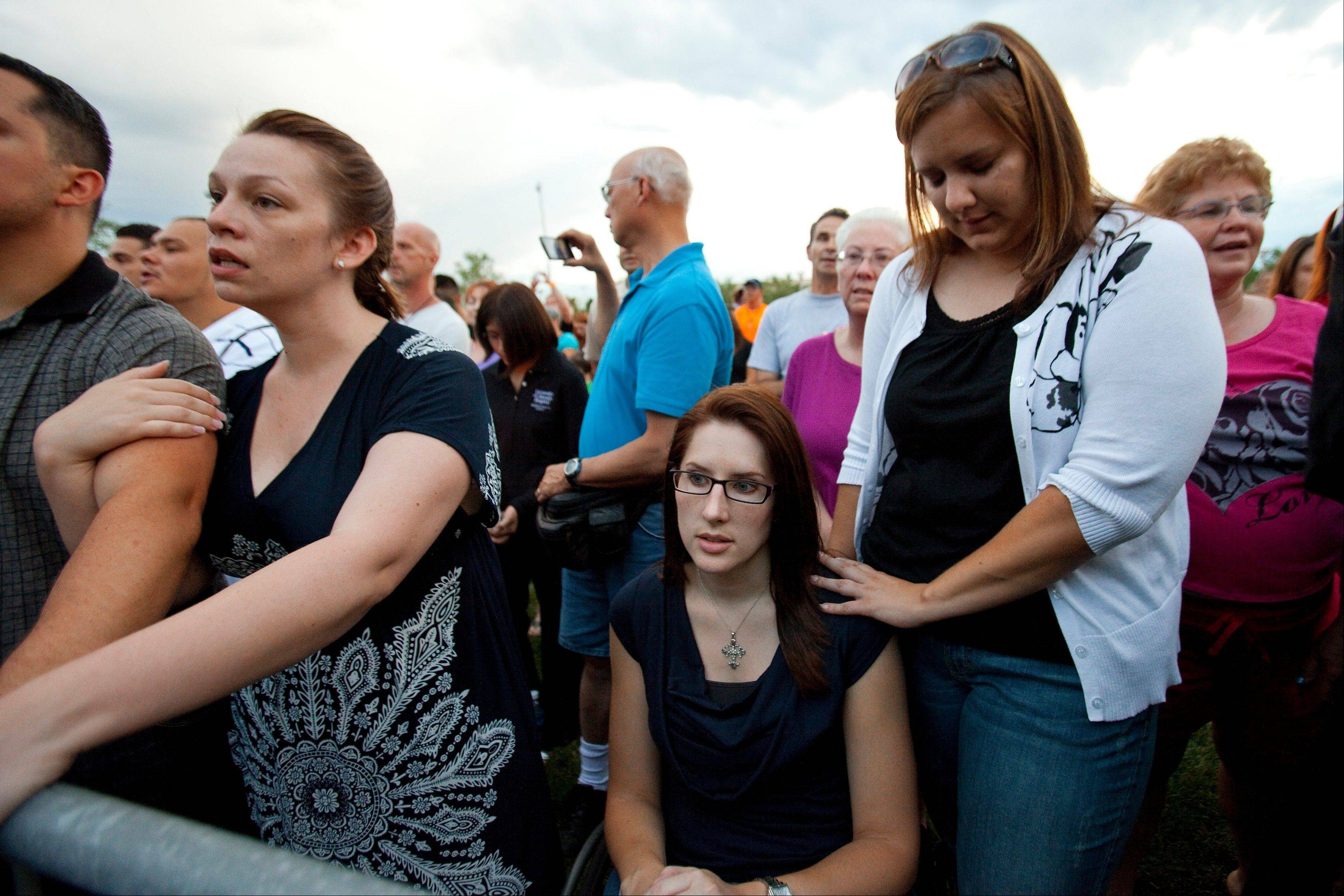 Anne Marie Hochhalter, 30, bottom, a paralyzed victim of the Columbine High School tragedy more than 12 years ago, and her friend Roxy Chesser, 30, second from right, attend a prayer vigil Sunday in Aurora, Colo., held to remember the lost and injured in Friday�s mass shooting at a movie theater.