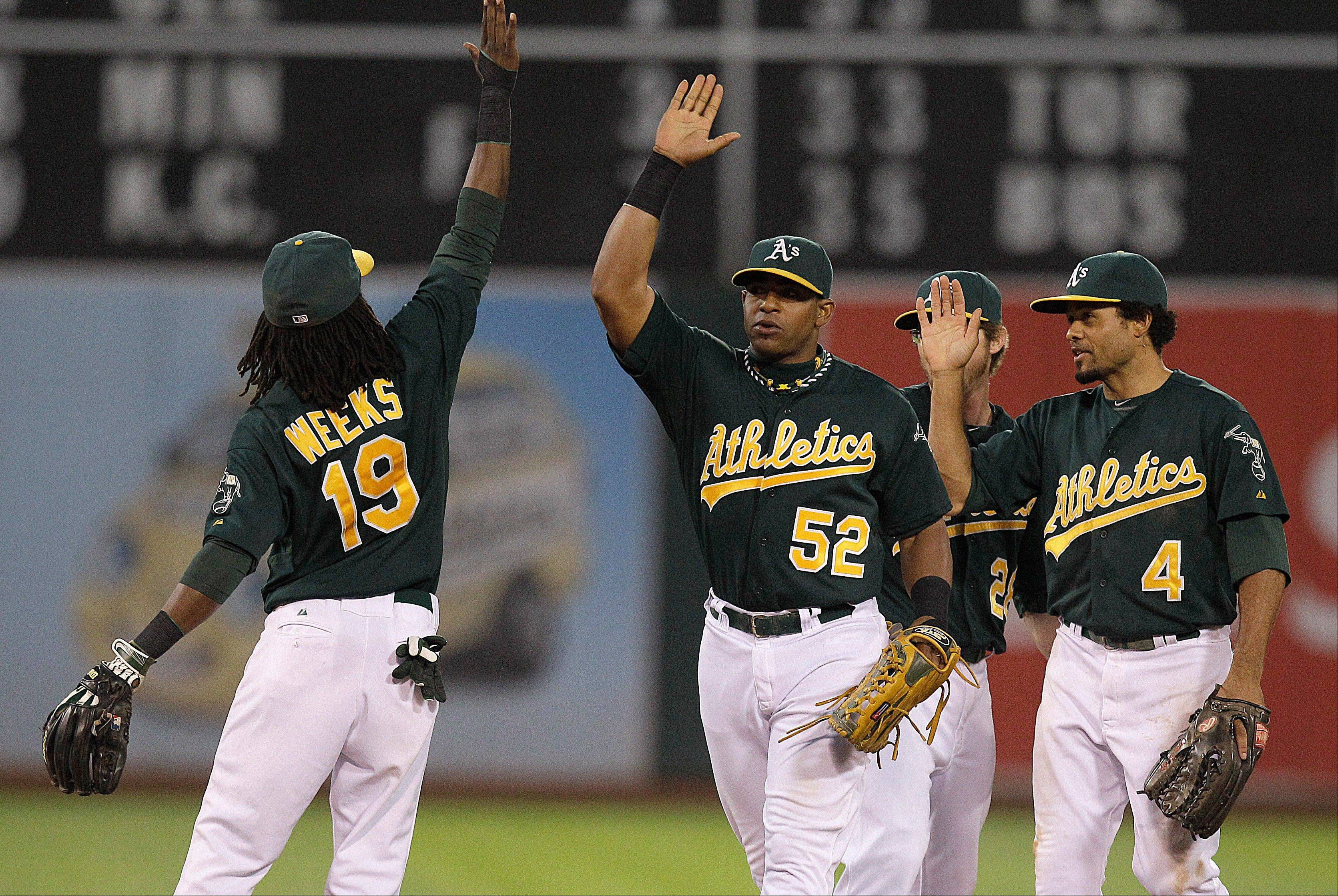 Oakland�s Jemile Weeks (19), Yoenis Cespedes (52) and Coco Crisp celebrate a 2-1 victory over New York on Saturday at home. The low-budget A�s swept the four-game series against the $200 million Yankees.