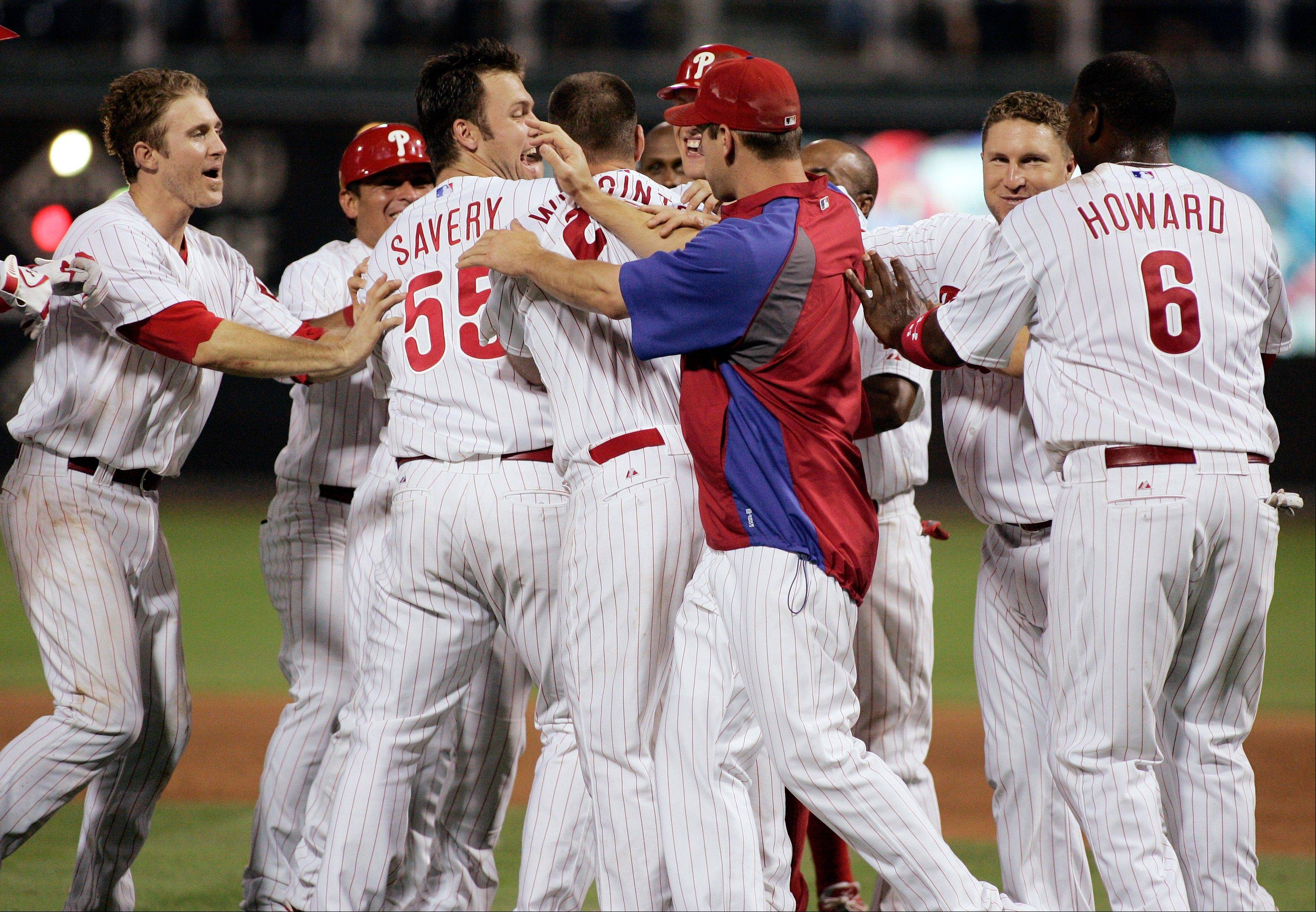 The Phillies swarm around Ty Wigginton after his sacrifice fly scored Erik Kratz in the bottom of the ninth inning Monday night to beat Milwaukee.